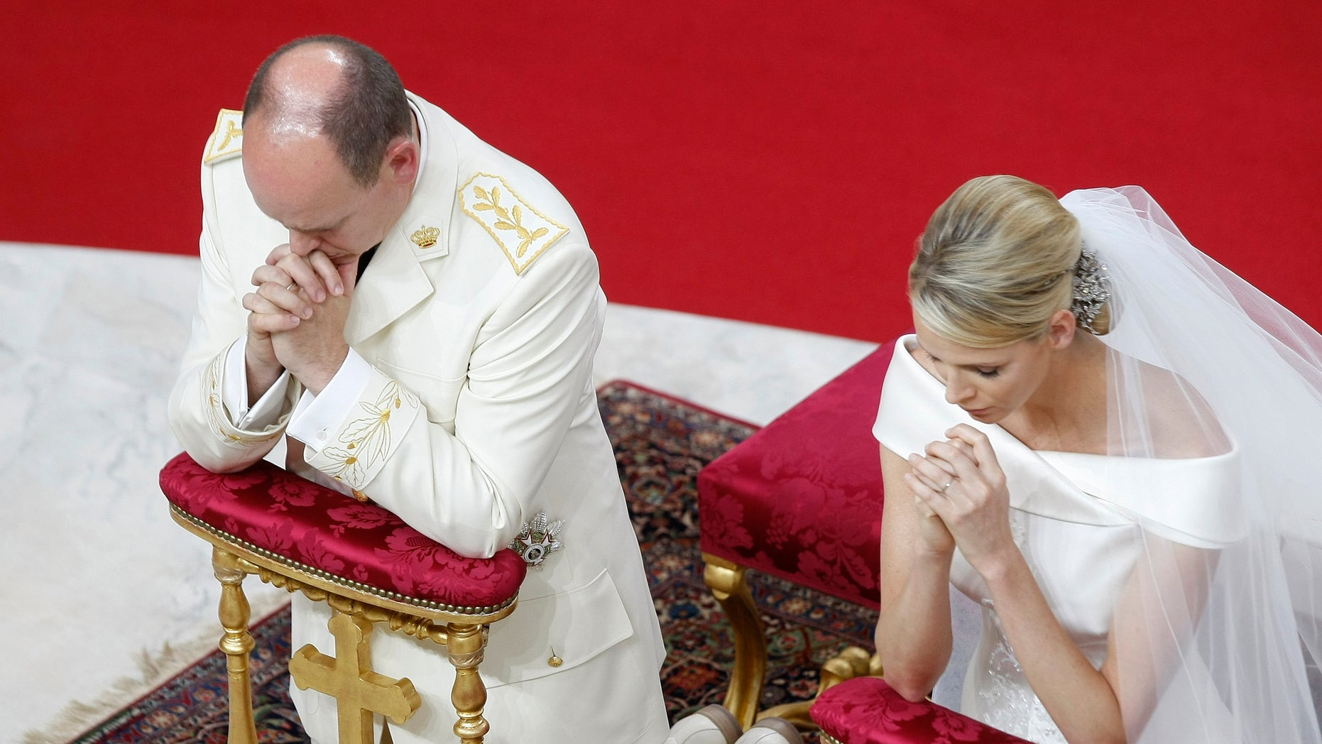 Prince Albert II of Monaco and Charlene Princess of Monaco kneel in prayer during their religious wedding ceremony at the Monaco palace, Saturday, July 2, 2011.
