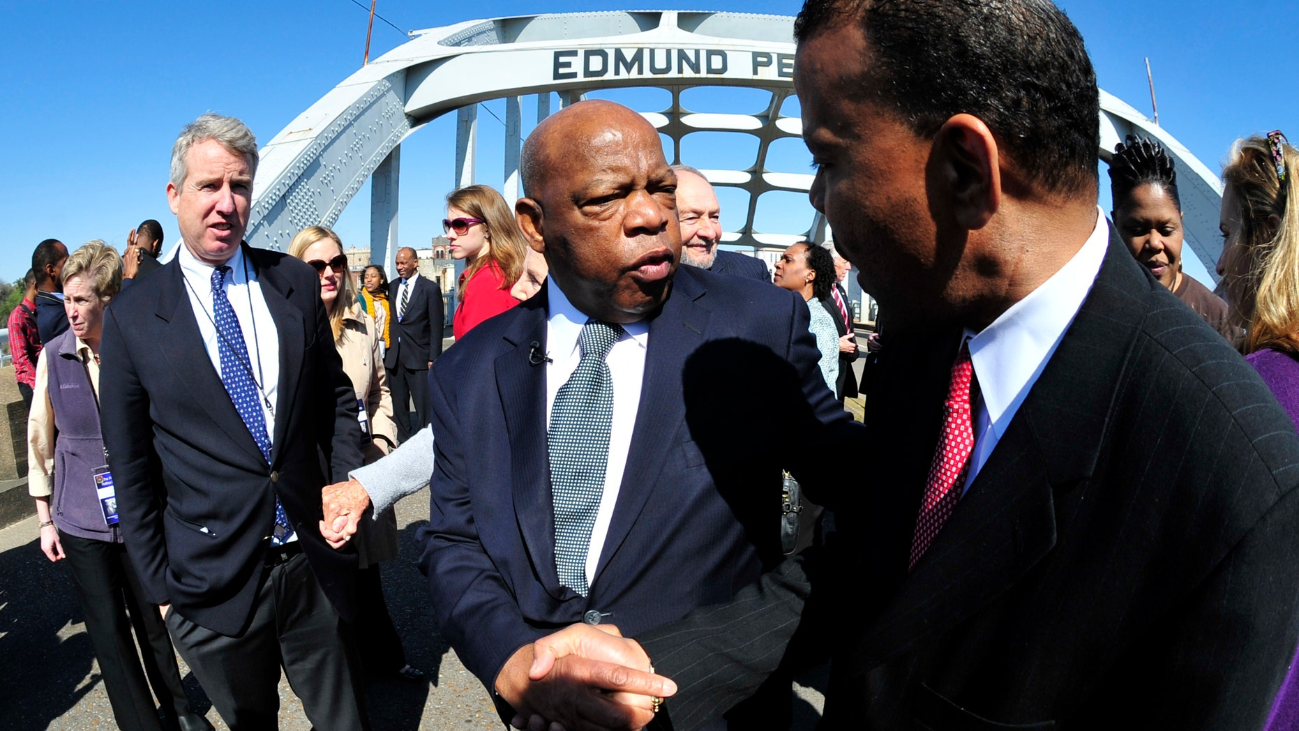 "U.S. Rep. John Lewis, D-Ga., center, is greeted by a well wisher as he pauses for a photo opportunity with members of the the Kennedy family prior to the 47th recreation of the ""Bloody Sunday"" civil rights march from Selma to Montgomery across the Edmund Pettus Bridge in Selma, Ala., Sunday, March 4, 2012. (AP Photo/Kevin Glackmeyer)"