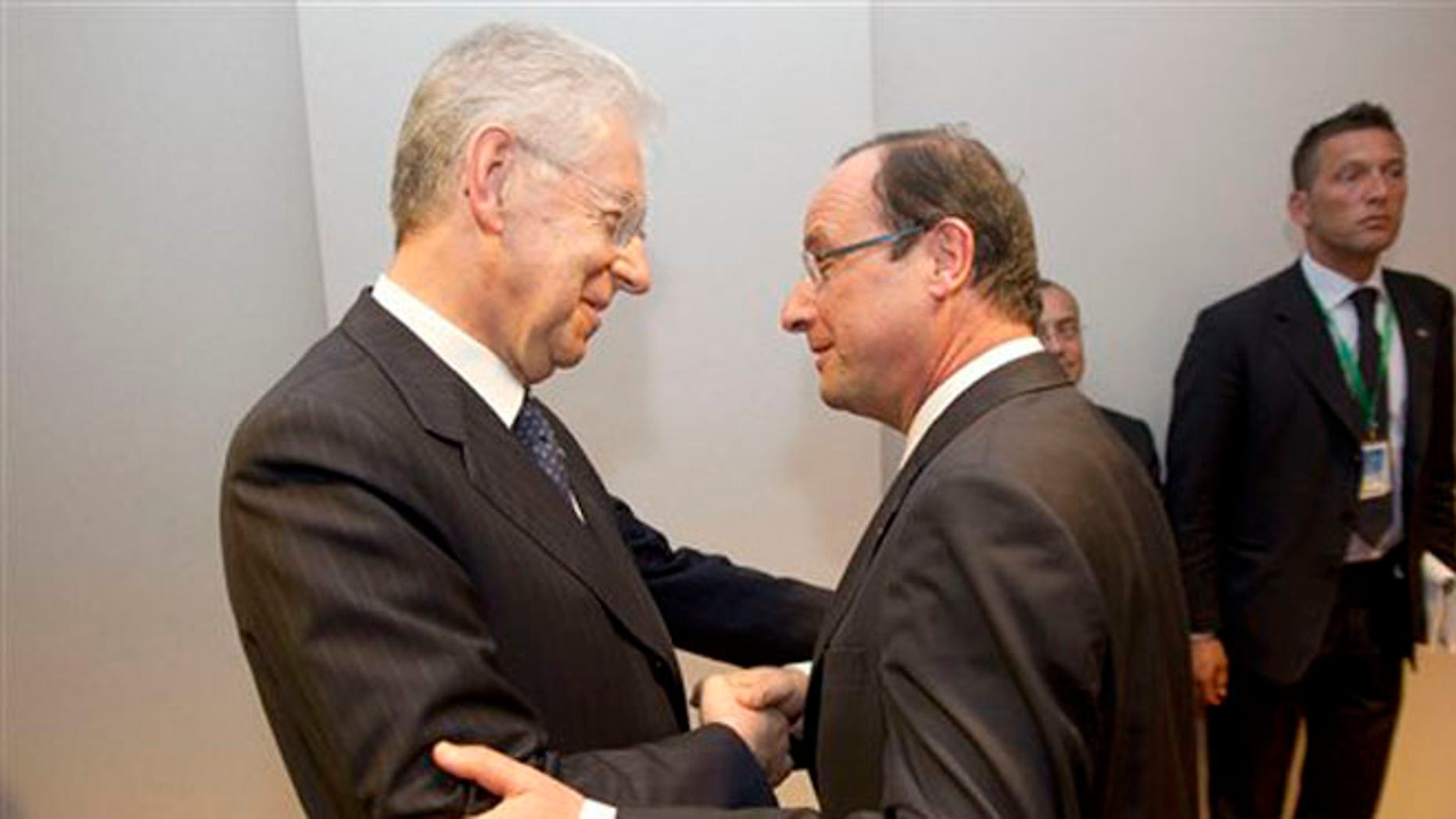 May 30, 2012: Italy's Prime Minister Mario Monti, left, shakes hands with French President Francois Hollande, right, prior to a bilateral meeting on sideline of an EU summit, at the European Council building in Brussels.