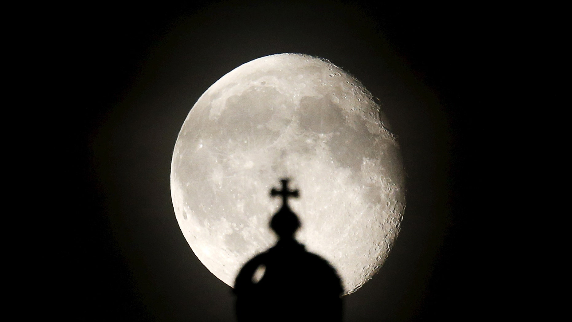 The moon rises next to a cross atop of the Reichstag building in Berlin, Germany, Aug. 2, 2015.