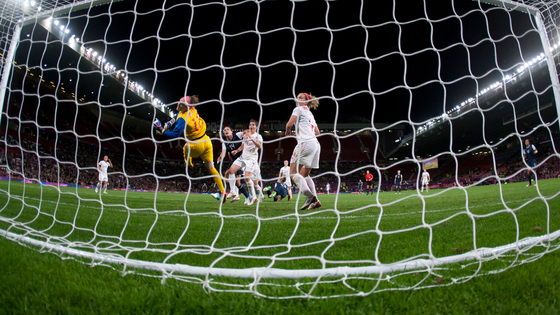 Aug. 6, 2012: Canada's goalkeeper Erin Mcleod, center left, dives in vain as the United States' Alex Morgan, bottom center, scores the winning goal during their semifinal women's soccer match at the 2012 London Summer Olympics at Old Trafford Stadium in Manchester, England.