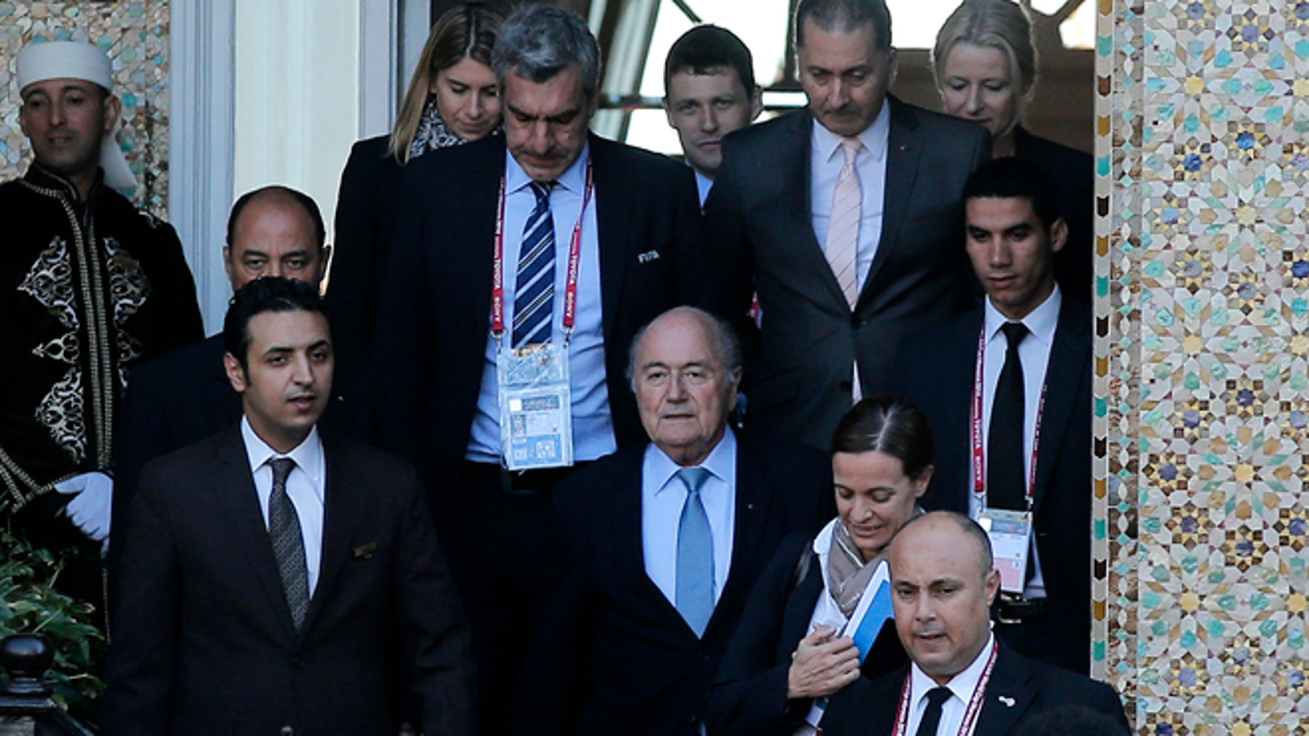 FIFA president Sepp Blatter, center, leaves a hotel to lead a meeting in Marrakech, Morocco, Thursday, Dec. 18, 2014. Amid another crisis at FIFA, Blatter will lead an executive committee meeting on Thursday with the sudden resignation of ethics prosecutor Michael Garcia now on the agenda. (AP Photo/Christophe Ena)