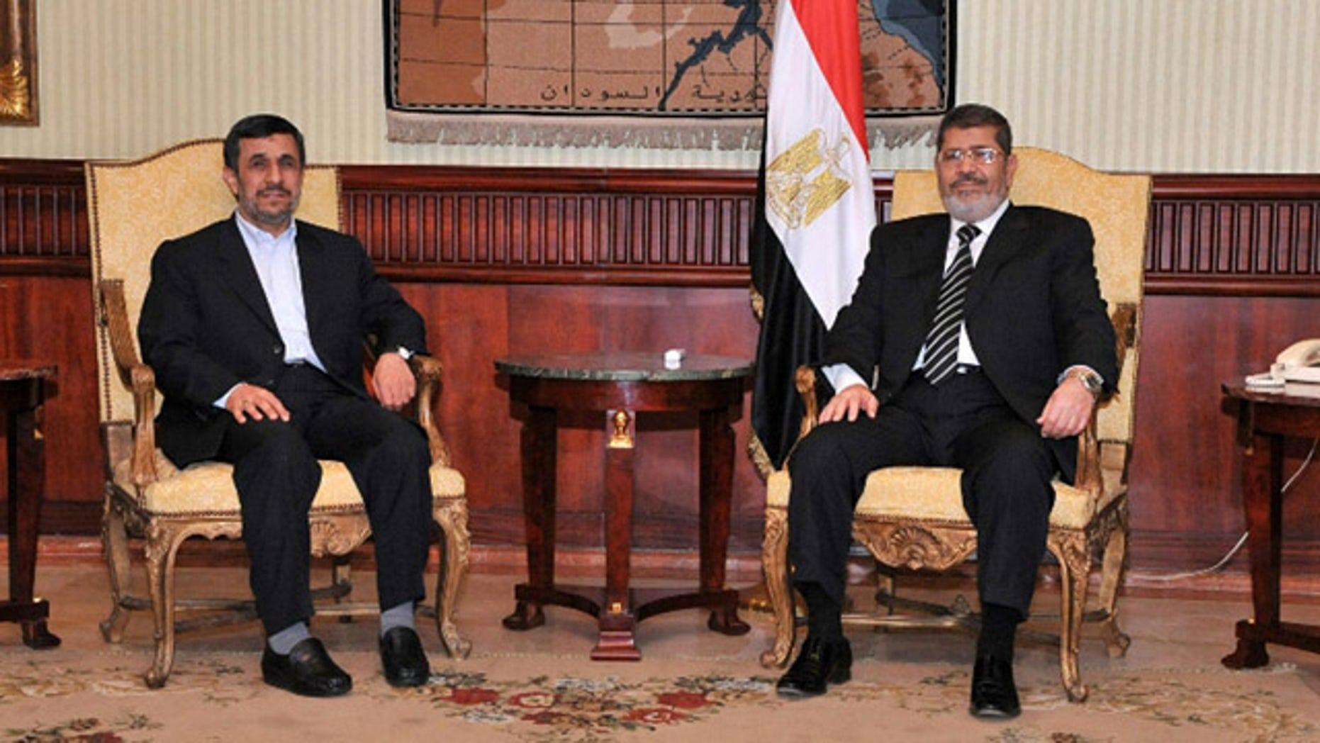 Feb. 5, 2013: Iran's President Mahmoud Ahmadinejad, left, and Egyptian President Mohammed Morsi, right, pose for photographers in Cairo, Egypt.