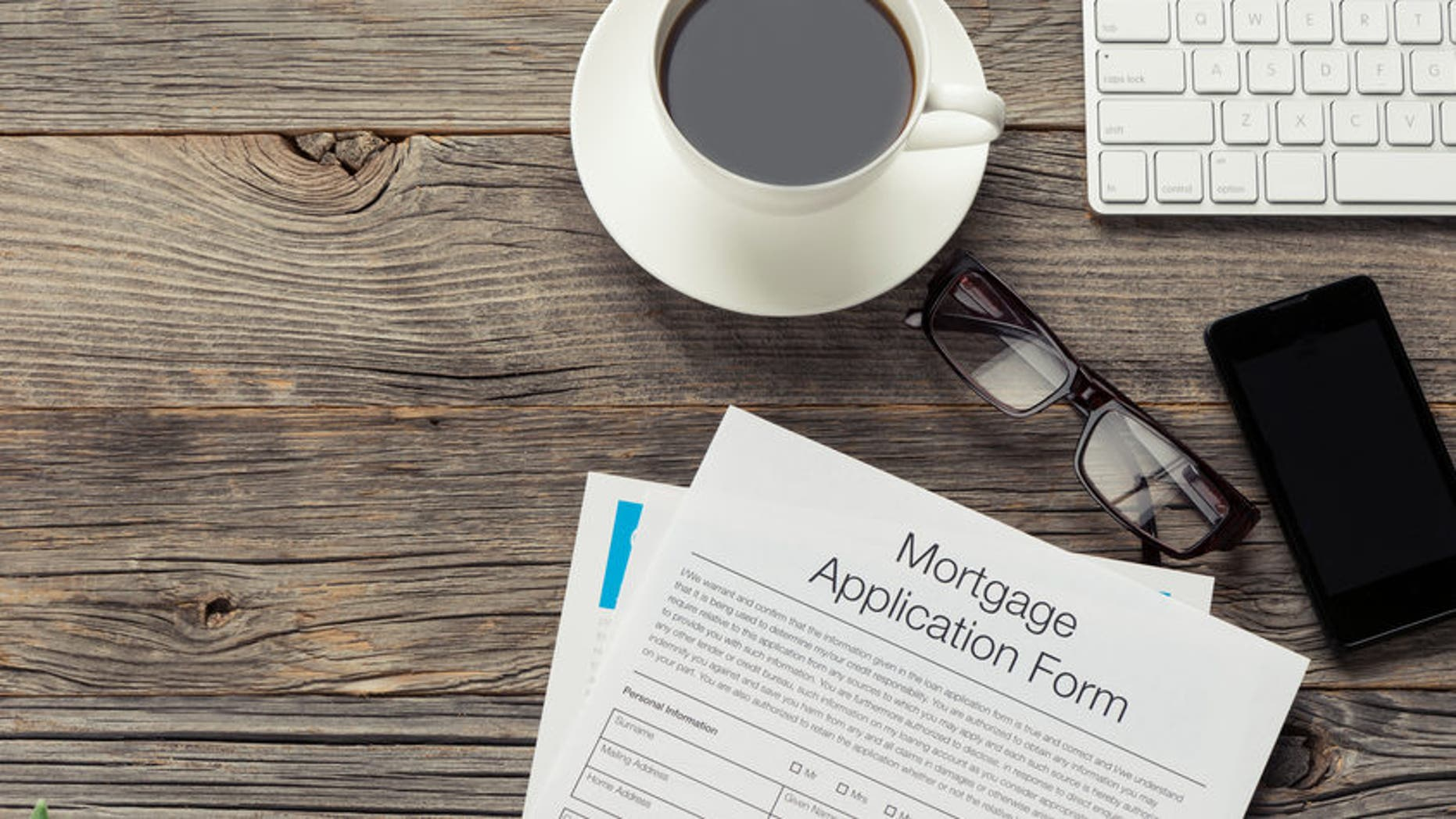 Mortgage application form on wooden table. There is also a mobile phone, computer keyboard, coffee, Filofax organizer notepad and glasses on the table. The table is made of wood and is quite old. Copy space on left.
