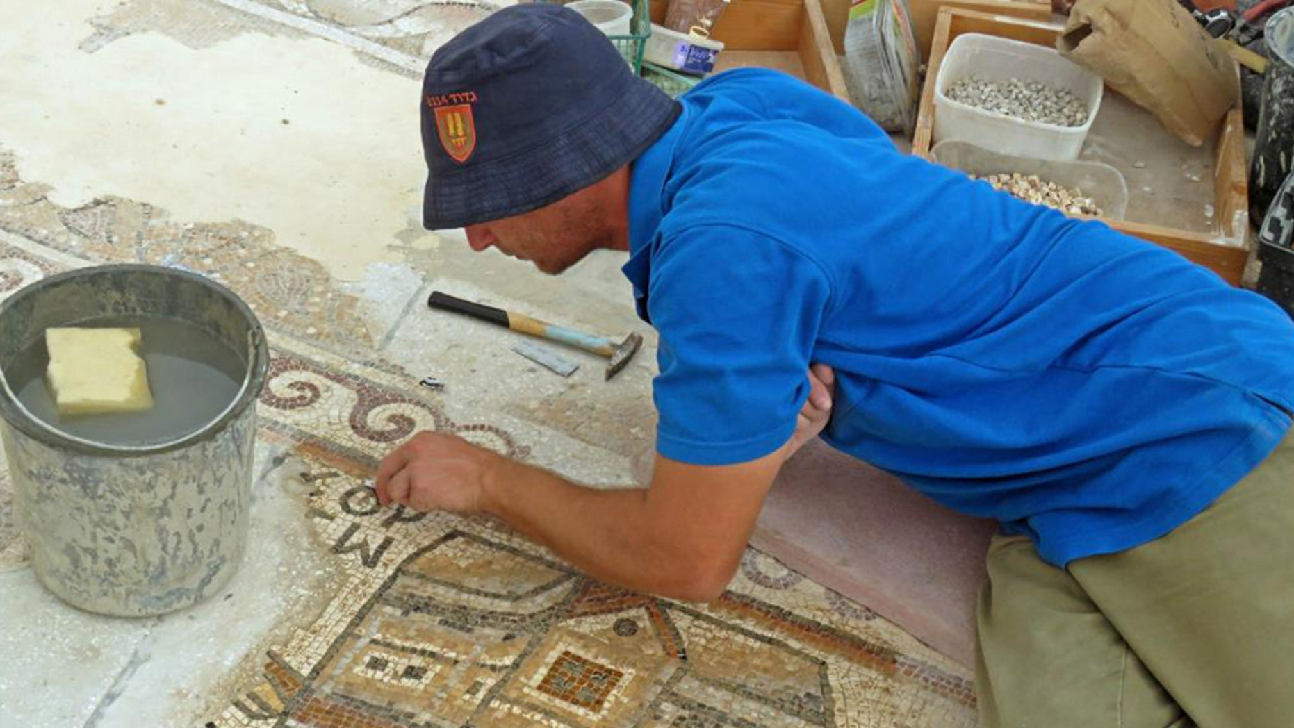 A worker of the Israel Antiquities Authority conserving the mosaic.