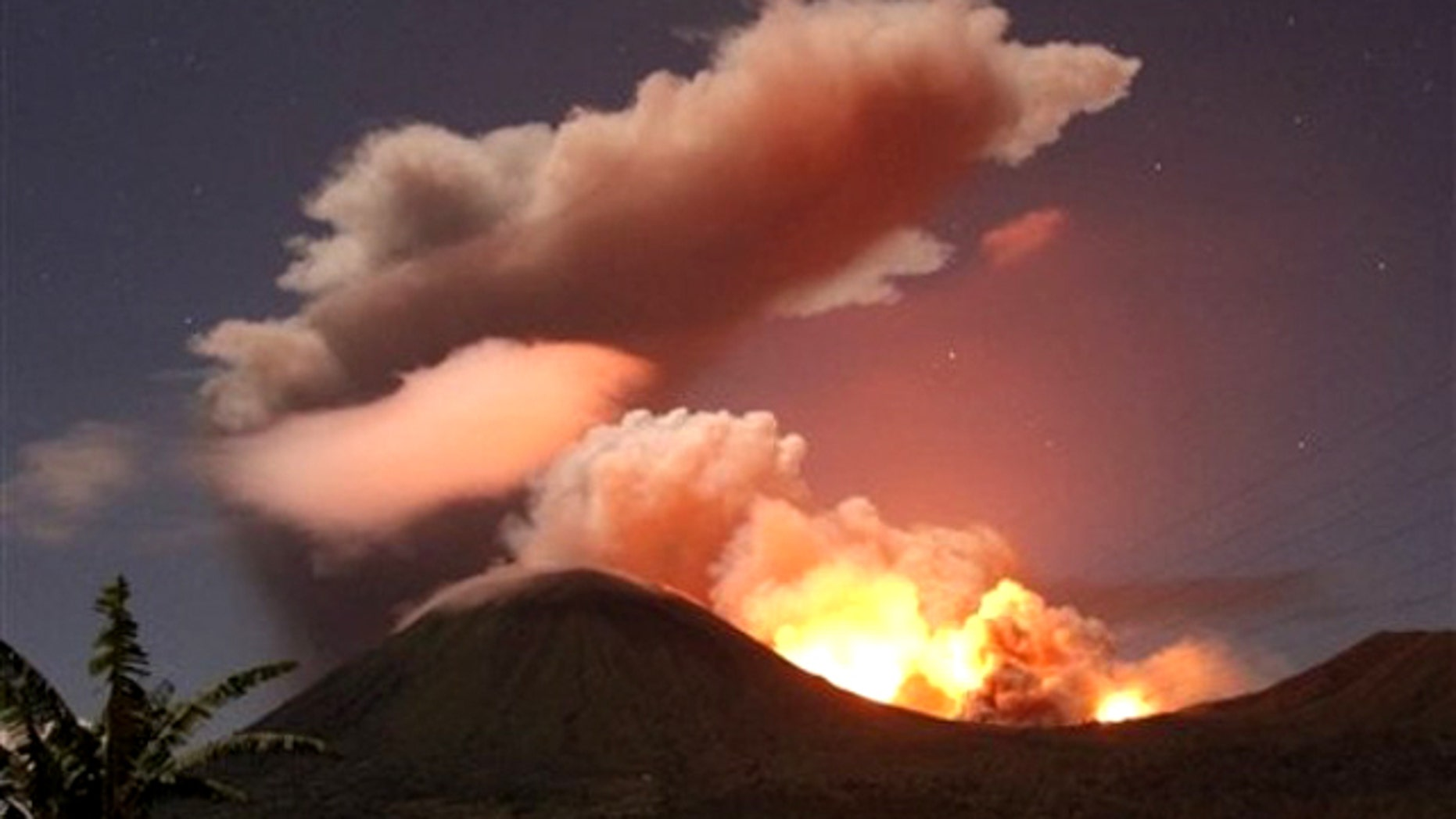 July 14, 2011: The glow of lava from Mount Lokon's eruption is seen against the night sky in July, 2011. The volcano erupted yet again early Tuesday, Dec. 27, 2011.