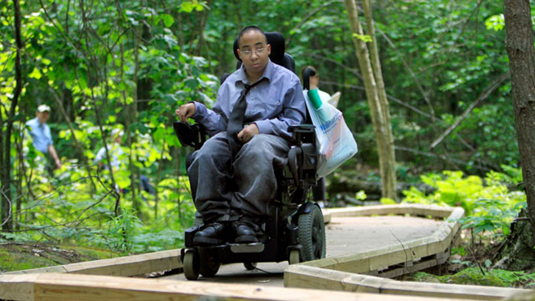 In this Thursday, June 16, 2011, photo, Chelsea Fernandez steers her wheelchair through the woods at the Crotched Mountain Rehabilitation Center in Greenfield, N.H. The center  offers  over 2.5 miles of  privately funded trails designed to be easily accessible for people in wheelchairs and those who have difficulty walking. (AP Photo/Jim Cole)