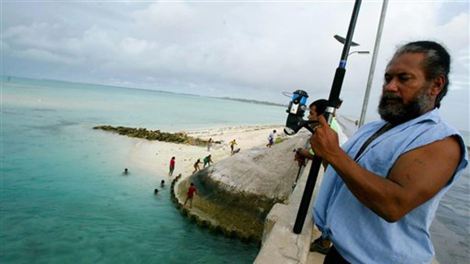 FILE - In this March 30, 2004 file photo, a man fishes on a bridge on Tarawa atoll, Kiribati.