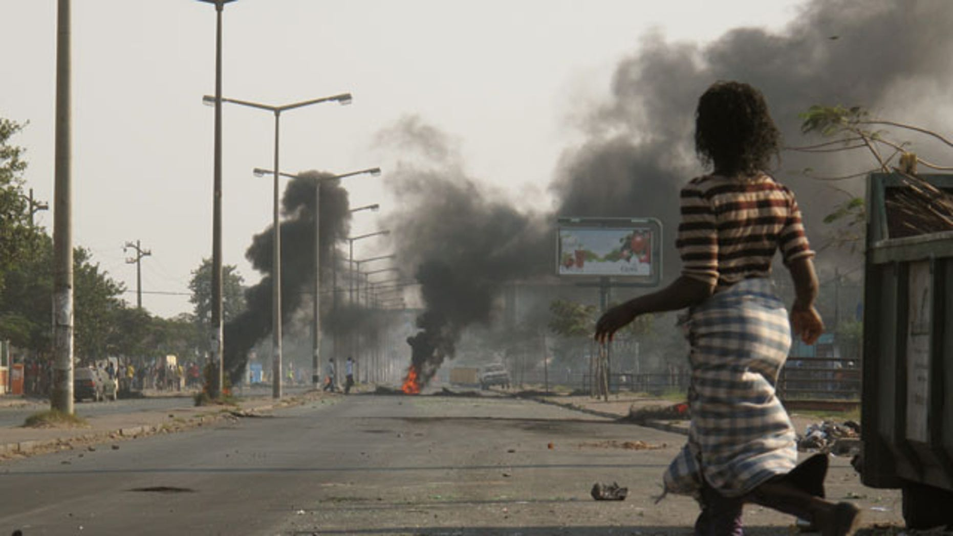 September 2: A woman passes nearby burning tires in a street in Maputo, Mozambique. (AP)