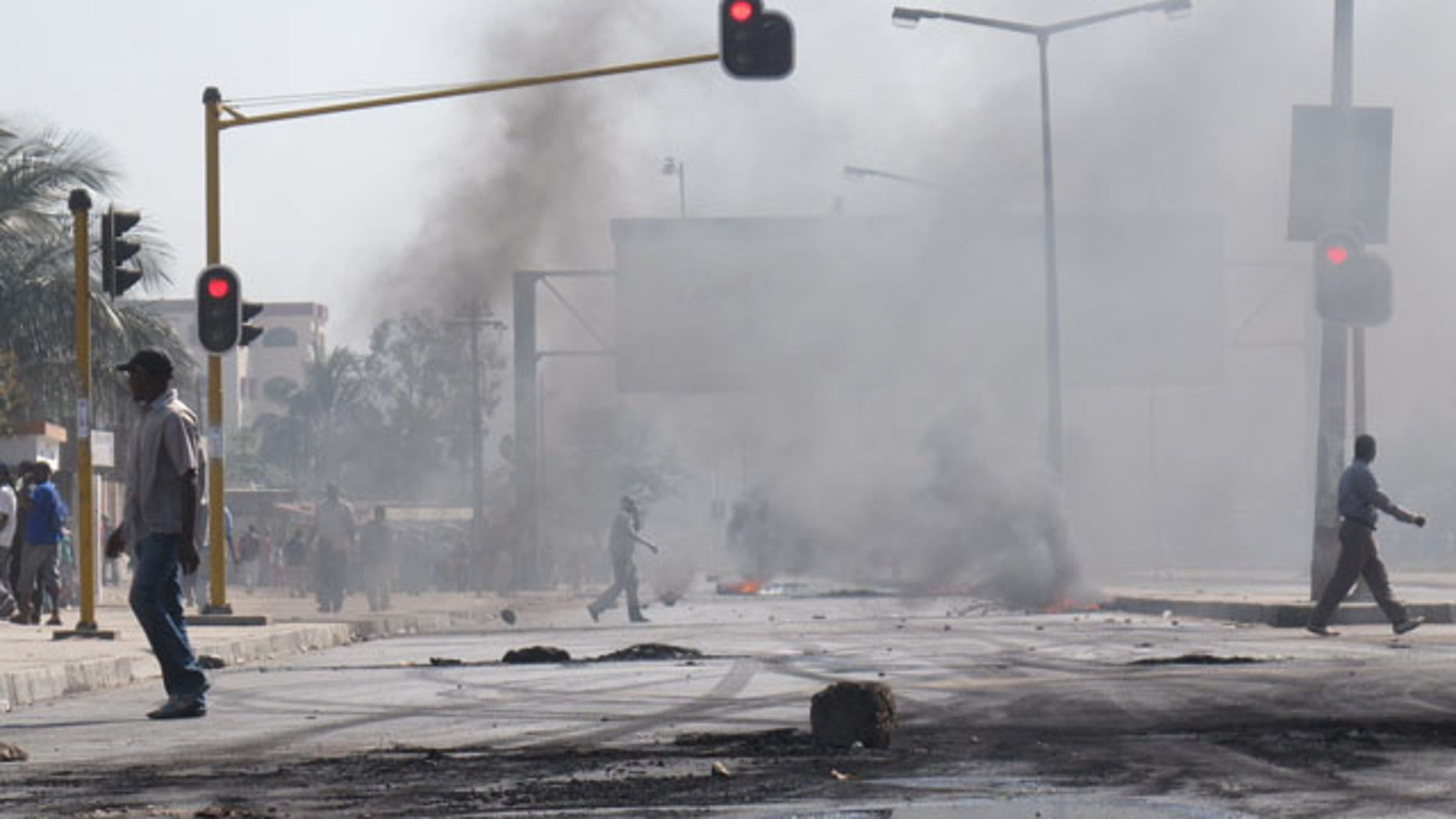 September 1: People walk past barricades of burning tires in Maputo, Mozambique after police opened fire on stone-throwing crowds who were protesting rising prices in this impoverished country. (AP)