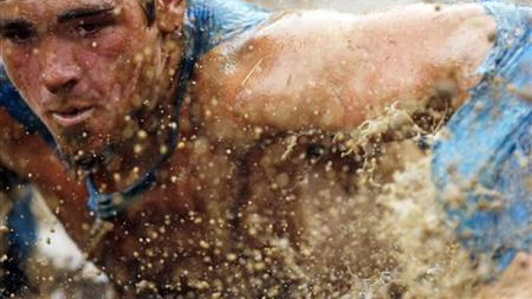 July 15, 2012: Mud flies in front of a competitor as he swims through mud underneath electrified wires during the Tough Mudder at Mt. Snow in West Dover, Vermont.