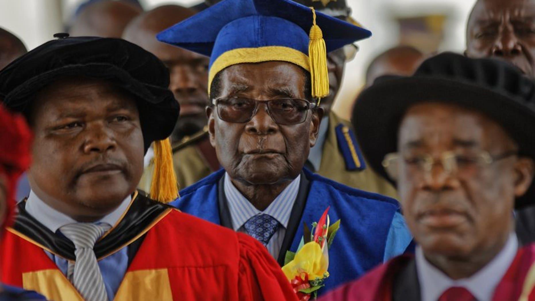 Zimbabwe's President Robert Mugabe, center, arrives to preside over a student graduation ceremony at Zimbambwe Open University, Nov. 17, 2017.