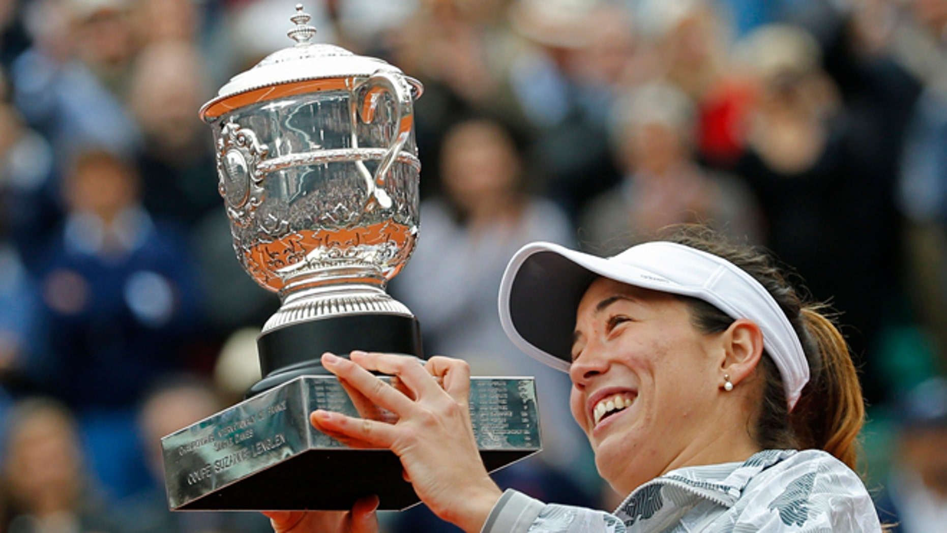 Spain's Garbine Muguruza holds the trophy after winning the final of the French Open tennis tournament against Serena Williams of the U.S. in two sets 7-5, 6-4, at the Roland Garros stadium in Paris, France, Saturday, June 4, 2016. (AP Photo/Alastair Grant)