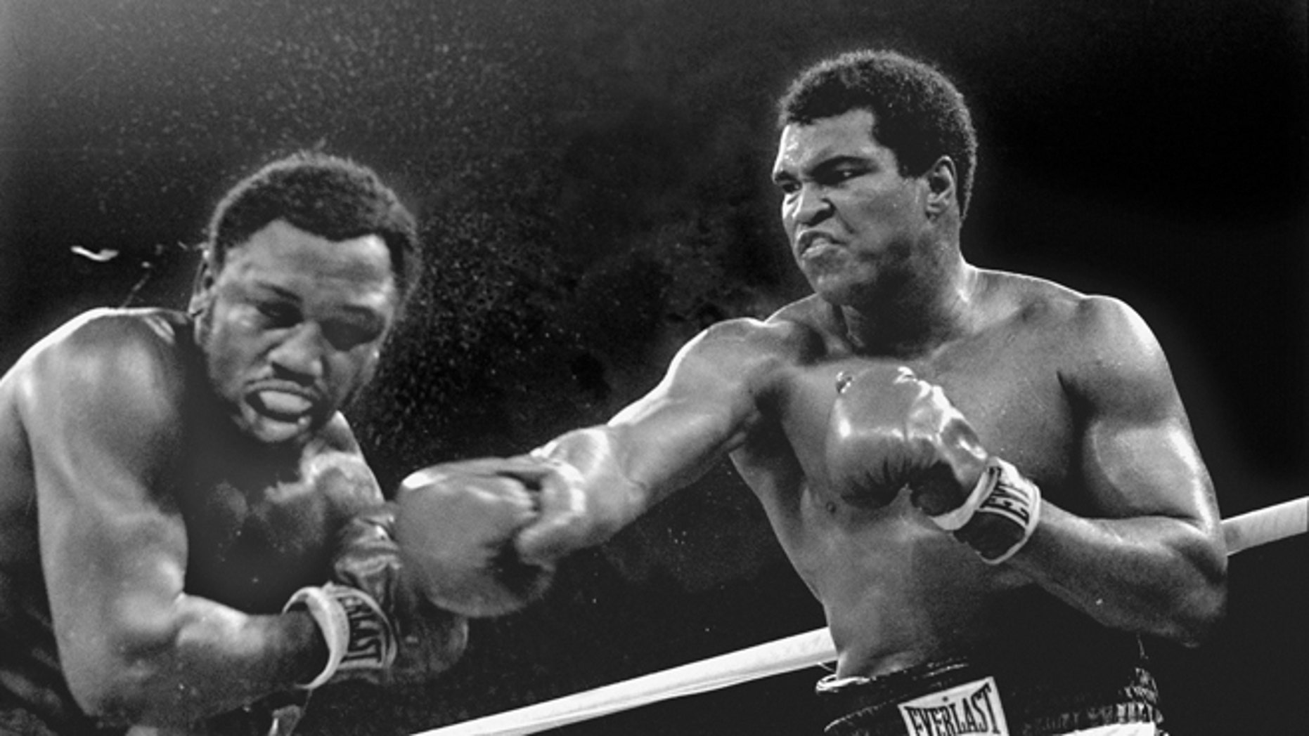 FILE-- Spray flies from the head of challenger Joe Frazier as heavyweight champion Muhammad Ali connects with a right in the ninth round of their title fight in Manila, Philippines, in this Oct. 1, 1975 file photo.  Ali won the fight on a decision to retain the title.  (AP Photo/Mitsunori Chigita)