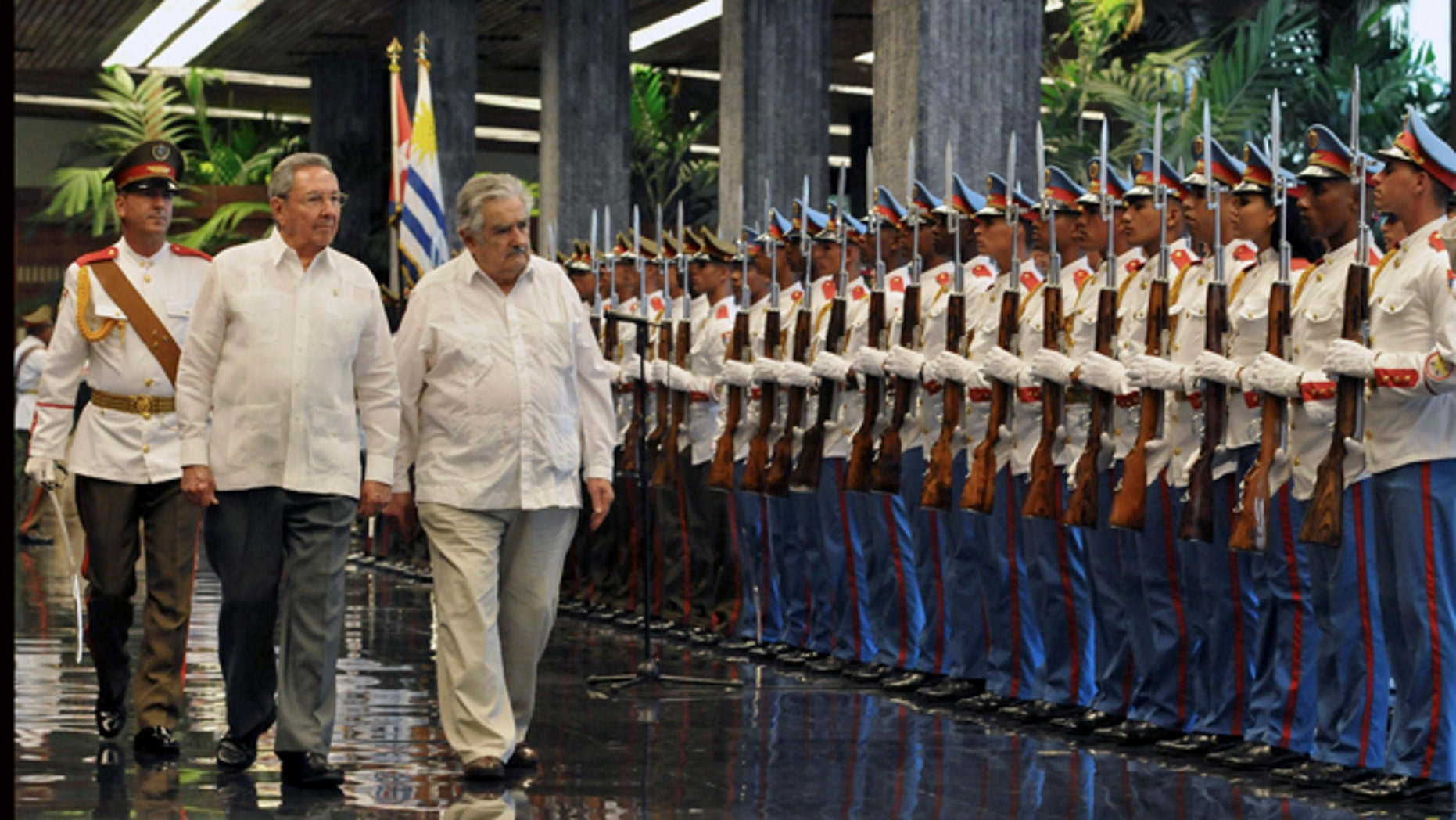 Cuba's President Raul Castro, left, and Uruguay's President Jose Mujica review the honor guard during a welcoming ceremony at Revolution Palace in Havana, Cuba, Wednesday, July 24, 2013. (AP Photo/Ernesto Mastrascusa, Pool)