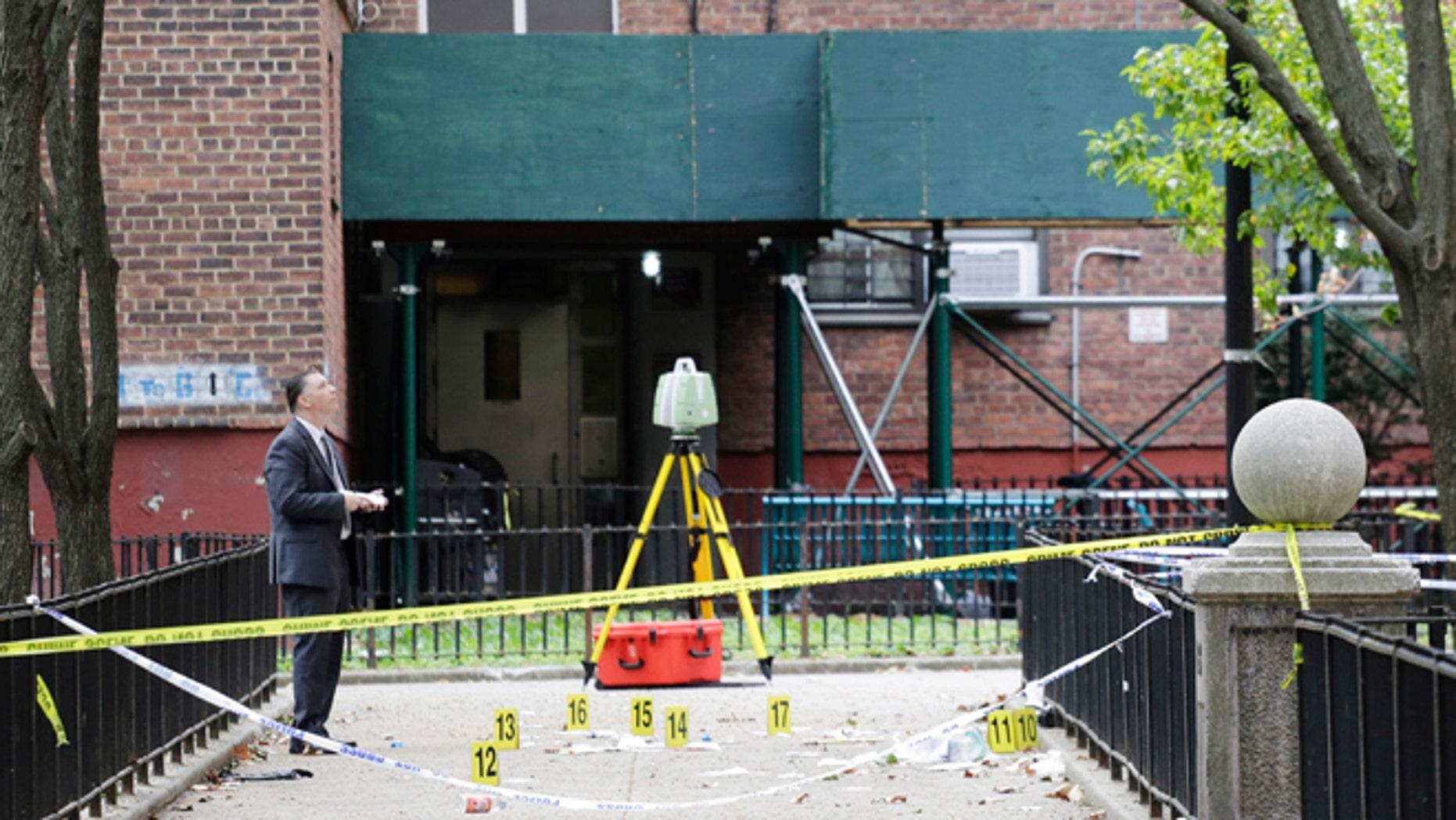 A New York City crime scene investigator inspects the scene of a triple homicide in Brooklyn.