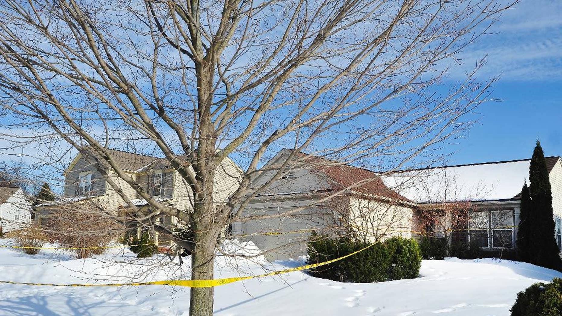 In this photo taken on March 7, 2014, police tape is scene outside a home in Pontiac, Mich., where the mummified body of a woman was found in the garage. Paula Logan has said the body found last week in Pontiac is that of Pia Farrenkopf, her sister. Authorities investigating the discovery haven't released her name, but they have said that the woman apparently died in 2008 at the age of 49. The Detroit Free Press reports voting records show Farrenkopf as voting in the November 2010 gubernatorial election. Officials say, however, that it may represent an administrative error. (AP Photo/Detroit News, Daniel Mears) DETROIT FREE PRESS OUT; HUFFINGTON POST OUT; MAGS OUT MANDATORY CREDIT.