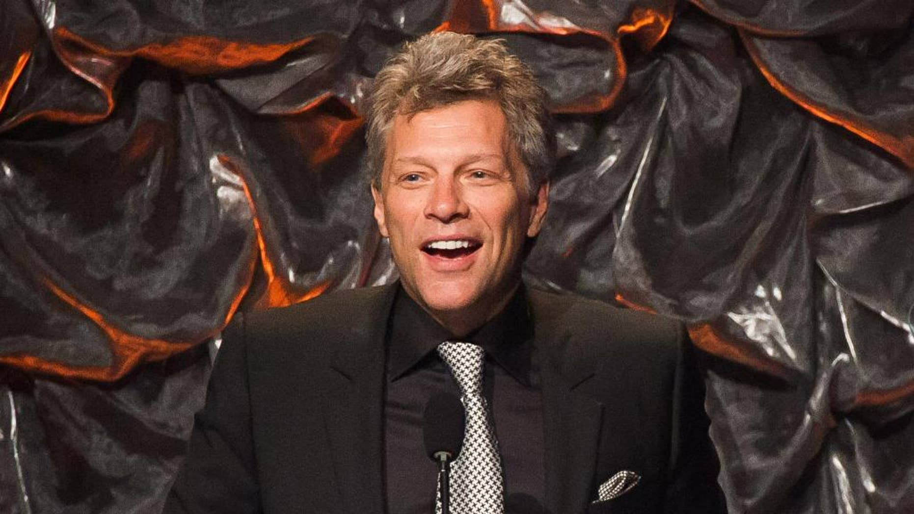 """FILE - In this June 12, 2014 file photo, Jon Bon Jovi attends the Songwriters Hall of Fame Awards in New York.  Promoters of Bon Jovi's upcoming shows in Asia said they are being canceled for """"unforeseen reasons."""" AEG Live Asia said in a statement Tuesday, Sept. 8, 2015 that refunds will be offered for shows scheduled for Sept. 14 in Shanghai and Sept. 17 in Beijing.(Photo by Charles Sykes/Invision/AP, File)"""