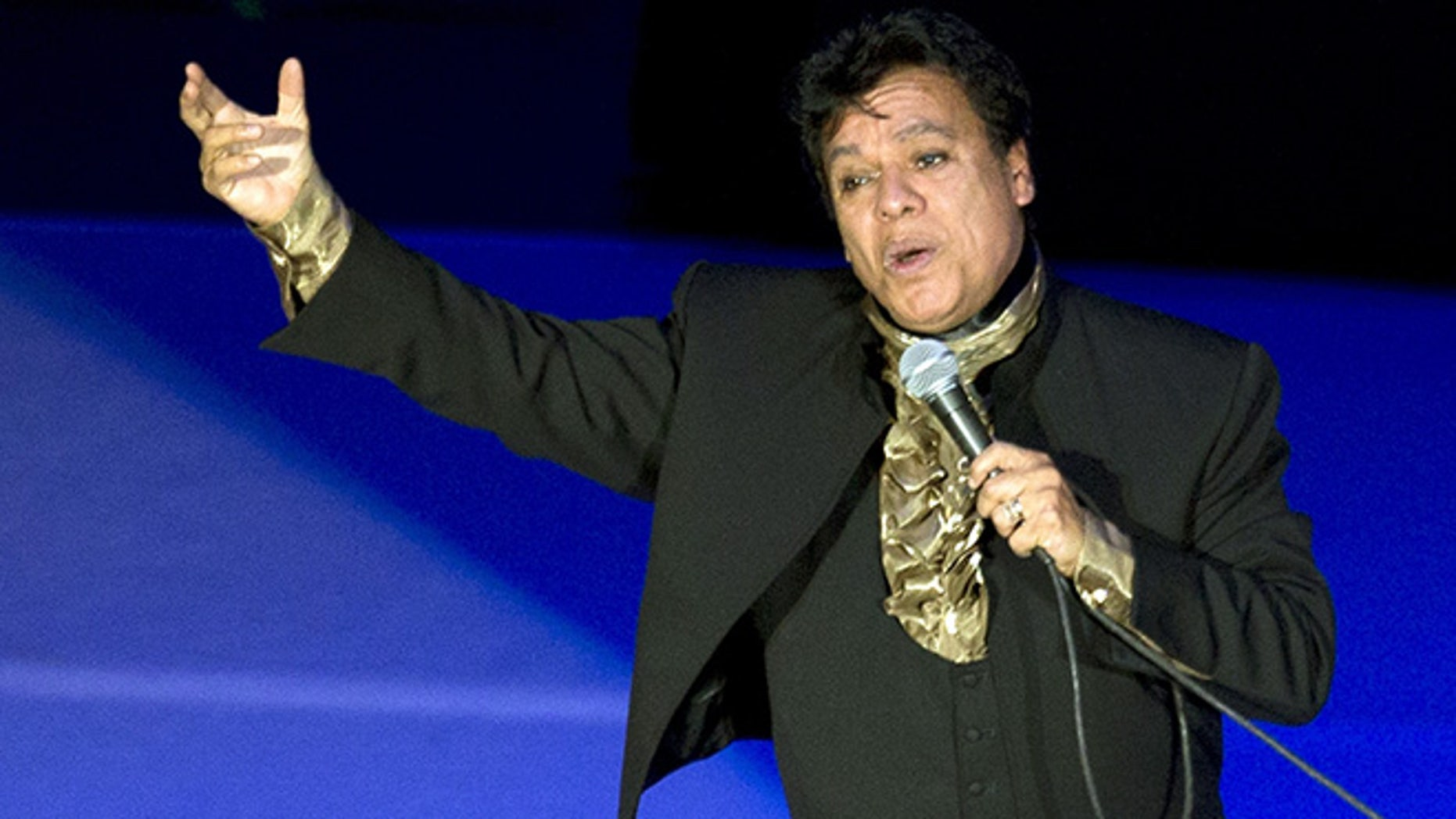 """FILE - In this April 10, 2015 file photo, Mexican singer-songwriter, Juan Gabriel, performs at the National Auditorium in Mexico City. Gabriel won the first Latin Grammy Award of his long career Thursday, Nov. 17, 2016, but presenter Andres Ceballos of the group Dvicio apparently didn't realize it was a posthumous prize. """"He's not here,"""" Ceballos said. """"The academy will make sure he receives this award."""" (AP Photo/Rebecca Blackwell, File)"""