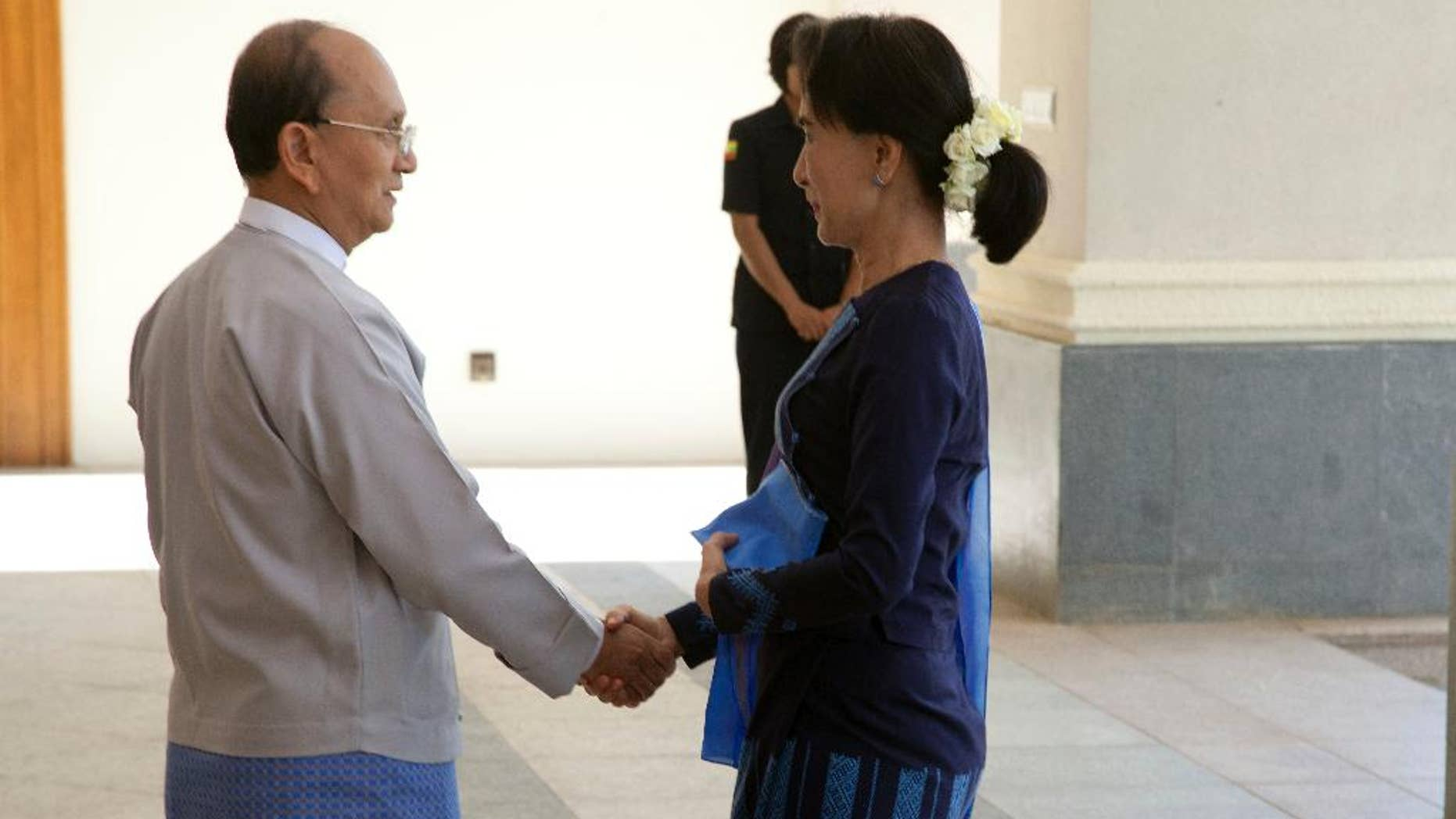 Myanmar President Thein Sein, left, shakes hands with Myanmar opposition leader Aung San Suu Kyi during their meeting at Myanmar Presidential Palace in Naypyitaw, Myanmar Friday, Oct 31, 2014. Myanmar's president is holding a rare meeting with Suu Kyi that also includes the country's political and military heavyweights. (AP Photo/Khin Maung Win)