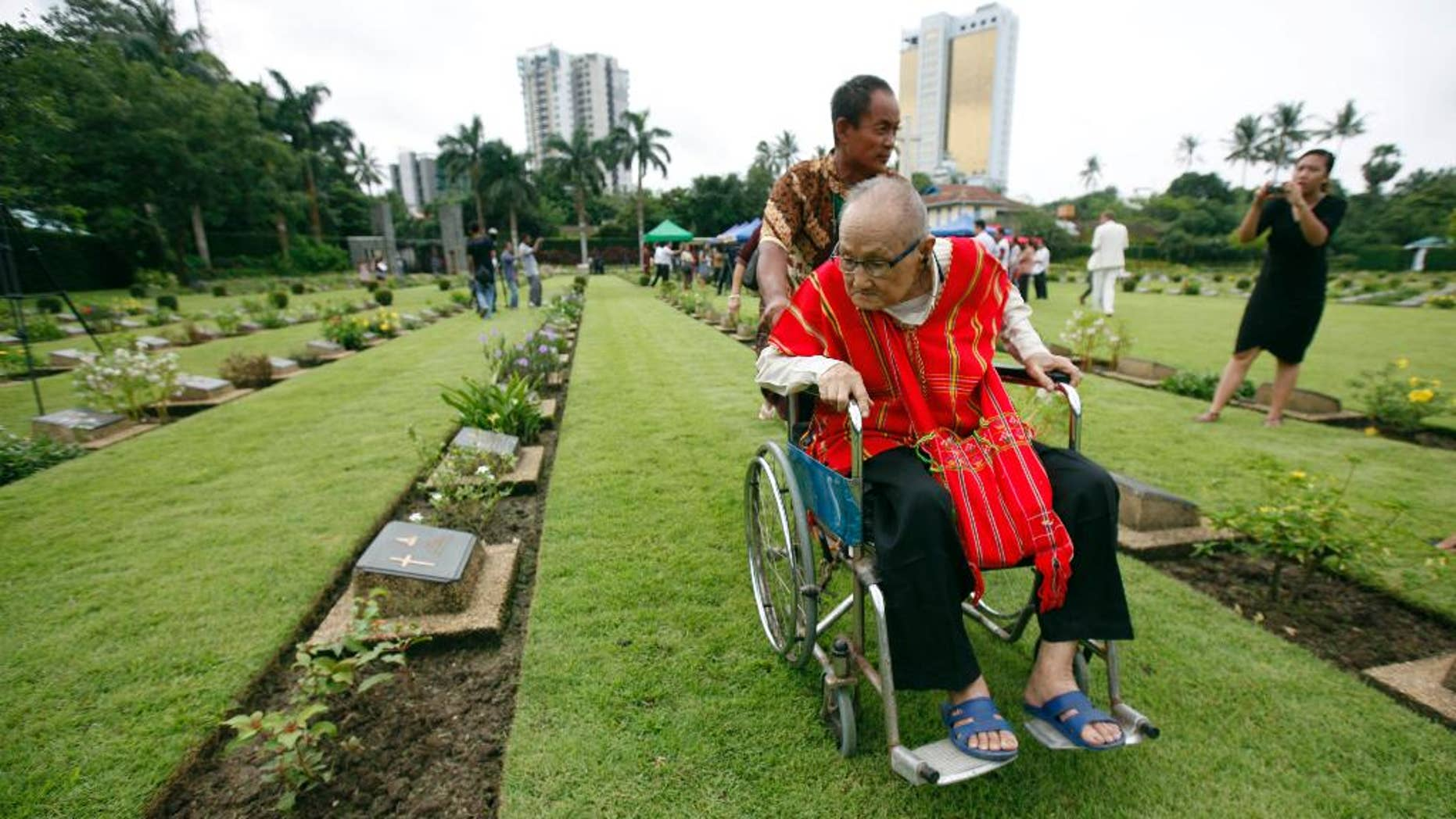 World War II veteran Saw Berny, who is ethnic Karen, looks at a gravestone as he attends a ceremony to mark the 70th anniversary of the end of World War II at Hanthawaddy War Cemetery in Yangon, Myanmar, Saturday, Aug. 15, 2015. Karen fought courageously behind Japanese lines with Seagrim, a lanky, eccentric and exceptional guerrilla leader. (AP Photo/Khin Maung Win)