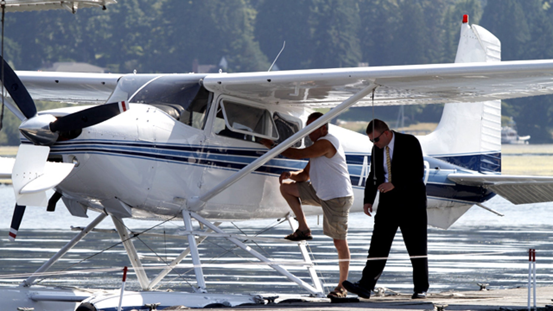 Lee Daily, left, is interviewed by an agent of the United States Secret Service at Kenmore Air Tuesday, Aug. 17, 2010 in Kenmore, Wash. Daily's float plane, crossing the Cascade mountain range headed to Seattle from Lake Chelan, violated the exclusion zone set up to protect President Barack Obama during his trip to the west coast. Daily was ordered to land at Kenmore Air Harbor.