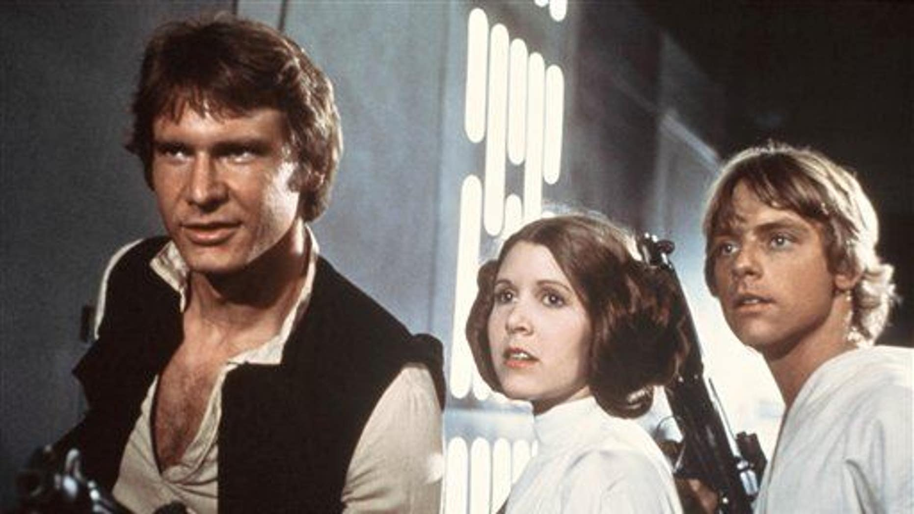 """This 1977 file image shows Harrison Ford, Carrie Fisher, and Mark Hamill in a scene from """"Star Wars."""""""