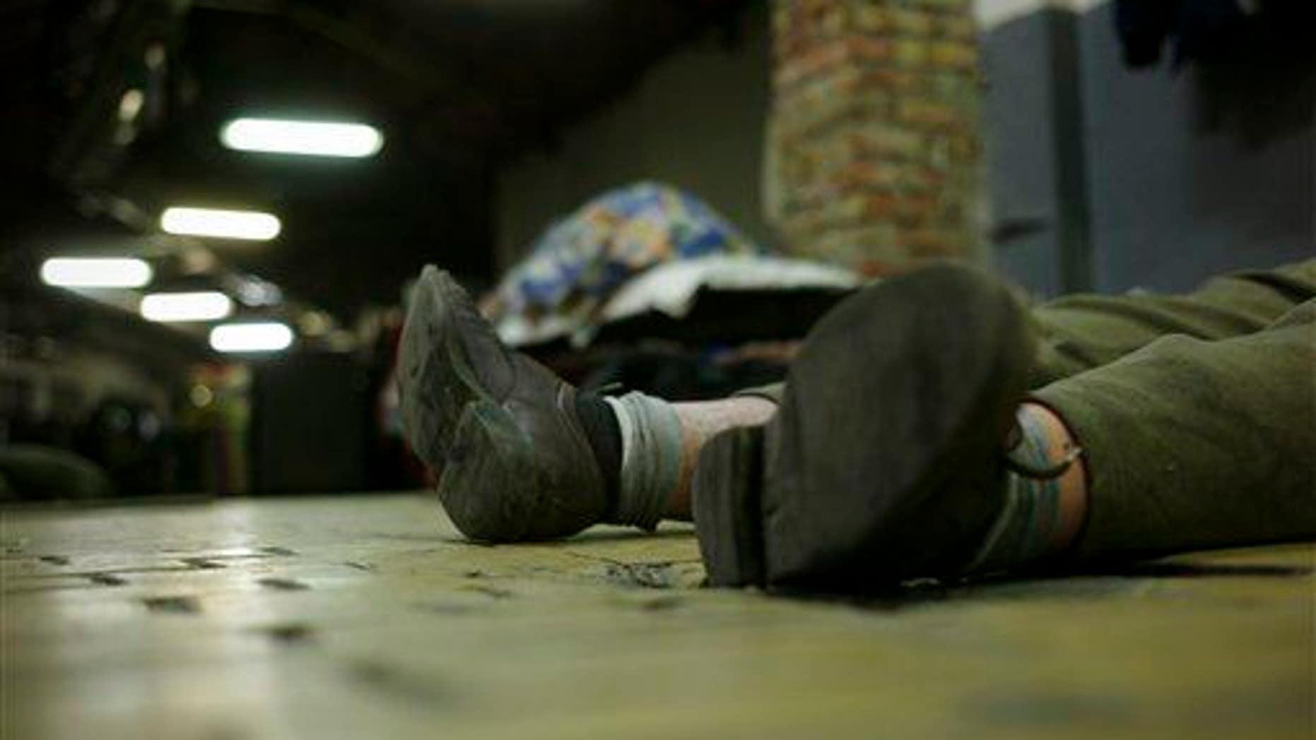 A man lies asleep on a floor.
