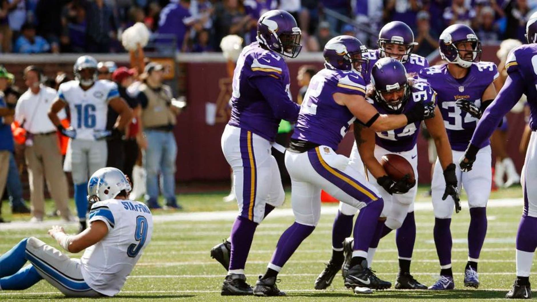 Sunday, Sept. 20: Minnesota Vikings defensive end Justin Trattou celebrates his interception as Detroit Lions quarterback Matthew Stafford sits on the field in the second half in Minneapolis. The Vikings won 26-16.