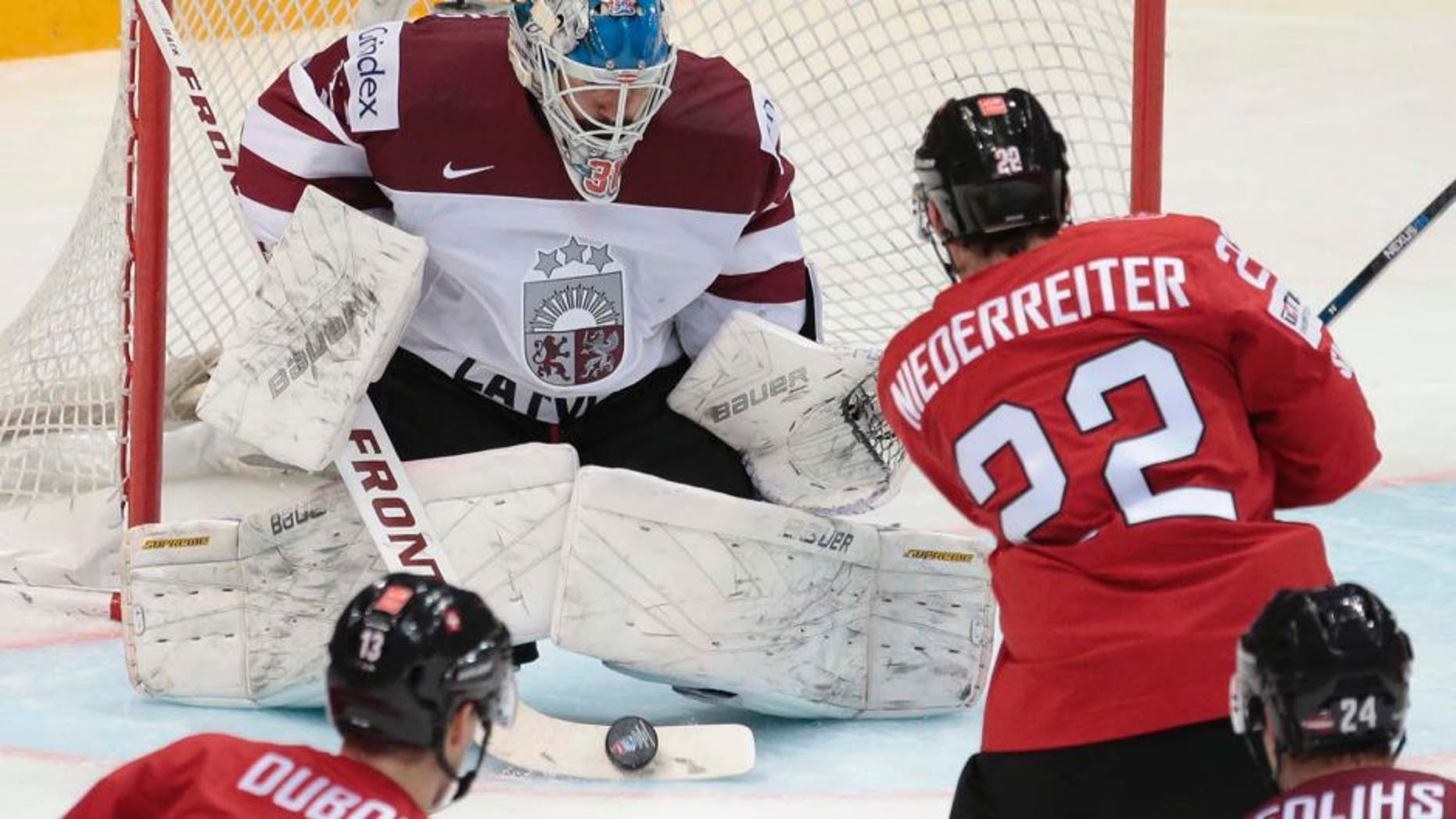Wednesday, May 11, 2016: Switzerland's Nino Niederreiter scores against Latvia's goalie Edgars Masalskis during the Ice Hockey World Championships Group A match between Switzerland and Latvia, in Moscow, Russia.