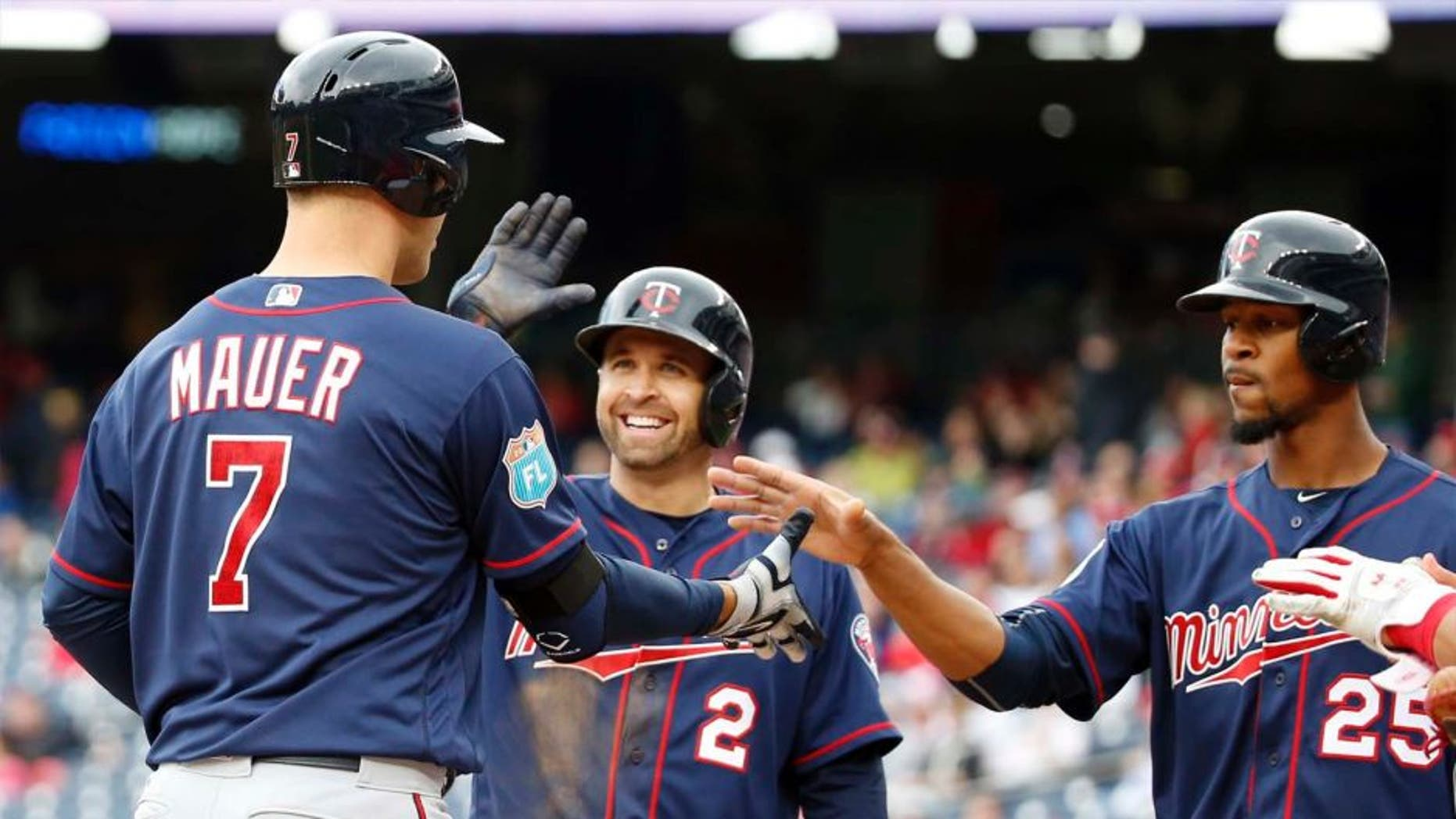 Saturday, April 2: The Minnesota Twins' Joe Mauer (left) celebrates knocking in Brian Dozier (center) and Byron Buxton with a three-run home run during the third inning of an exhibition baseball game against the Washington Nationals at Nationals Park in Washington.