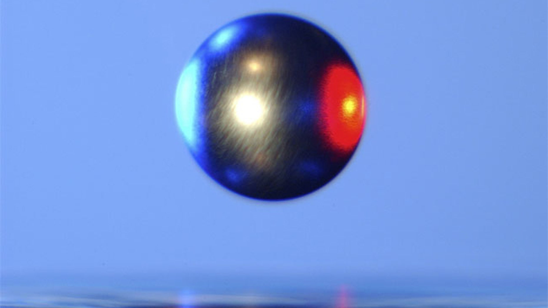 Inside a NASA Electrostatic Levitator, a ball of metal is suspended in mid-air by static electricity.