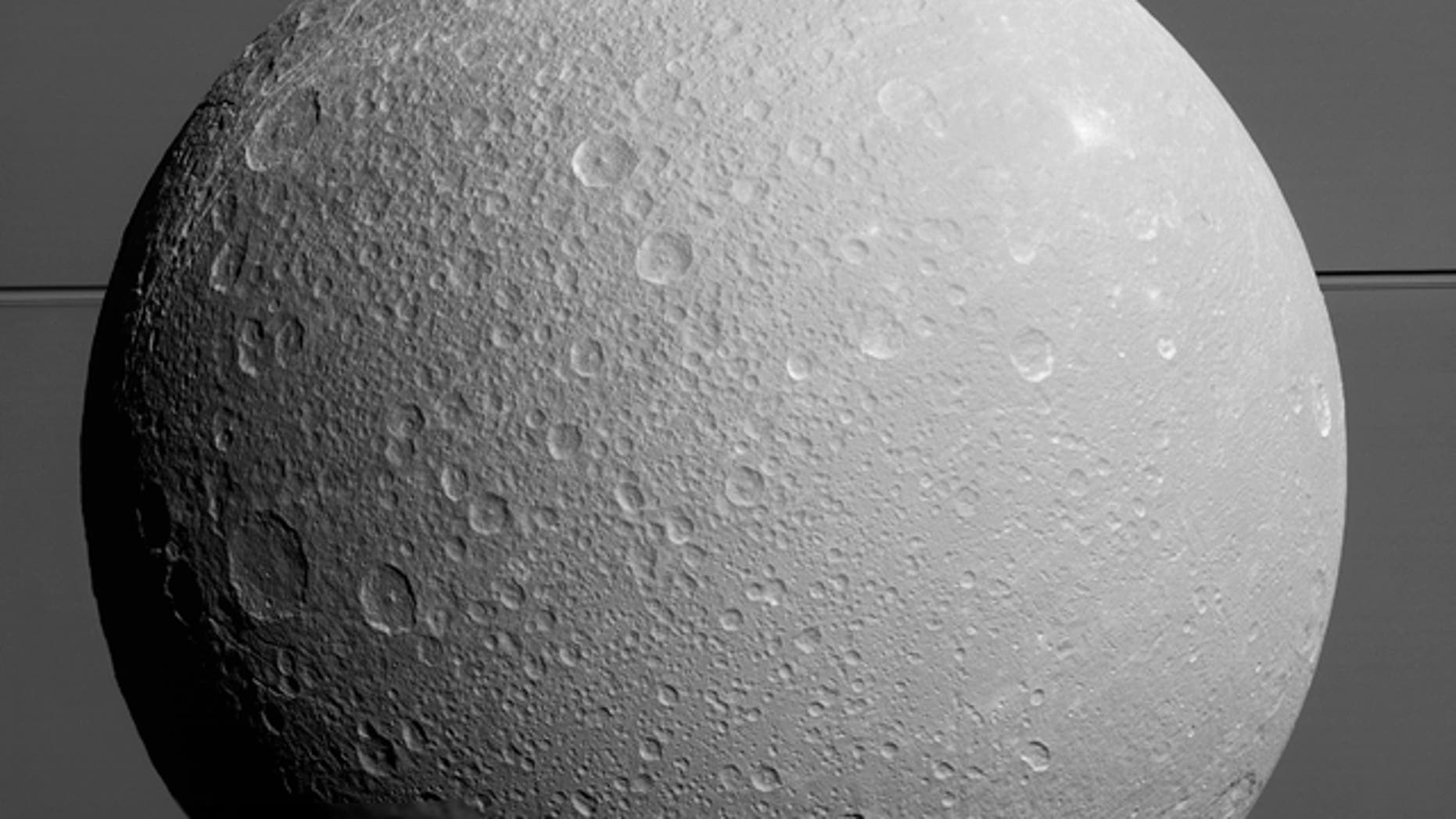 This view from NASA's Cassini spacecraft looks toward Saturn's icy moon Dione, with giant Saturn and its rings in the background, just prior to the mission's final close approach to the moon on August 17, 2015.