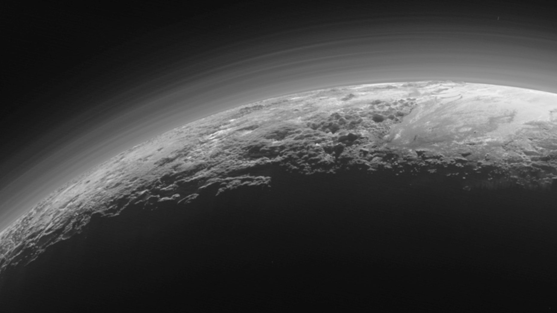 Just 15 minutes after its closest approach to Pluto on July 14, 2015, NASA's New Horizons spacecraft looked back toward the sun and captured this near-sunset view of the rugged, icy mountains and flat ice plains extending to Pluto's horizon.