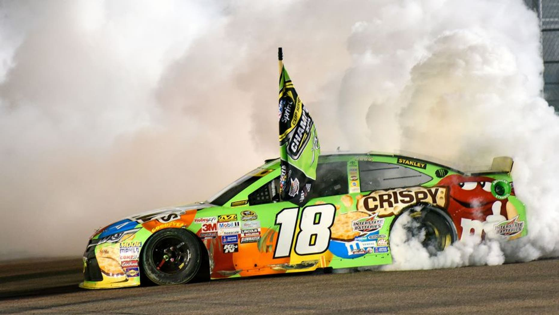 HOMESTEAD, FL - NOVEMBER 22: Kyle Busch, driver of the #18 M&M's Crispy Toyota, celebrates winning the series championship and the race with a burnout after the NASCAR Sprint Cup Series Ford EcoBoost 400 at Homestead-Miami Speedway on November 22, 2015 in Homestead, Florida. (Photo by Jared C. Tilton/NASCAR via Getty Images)