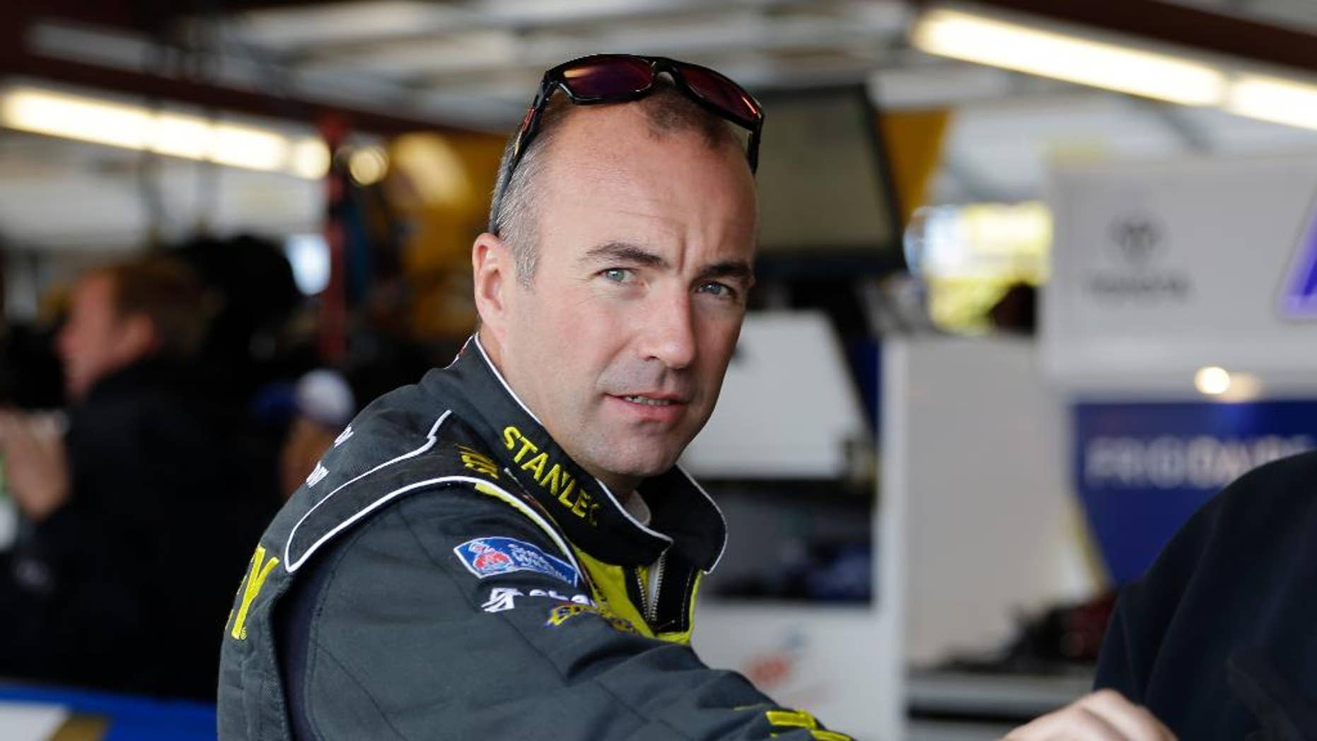 Driver Marcos Ambrose, of Australia, looks toward the outside from his garage during final practice for the NASCAR Sprint Cup Series auto race at Chicagoland Speedway in Joliet, Ill., Saturday, Sept. 13, 2014. Ambrose will leave NASCAR at the end of the season and return to his native Australia (AP Photo/Nam Y. Huh)