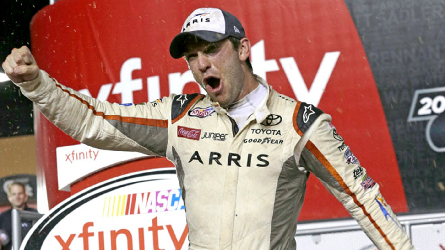 Daniel Suarez celebrates after wining the NASCAR Xfinity auto race and season title, Saturday, Nov. 19, 2016, in Homestead, Fla. (AP Photo/Terry Renna)