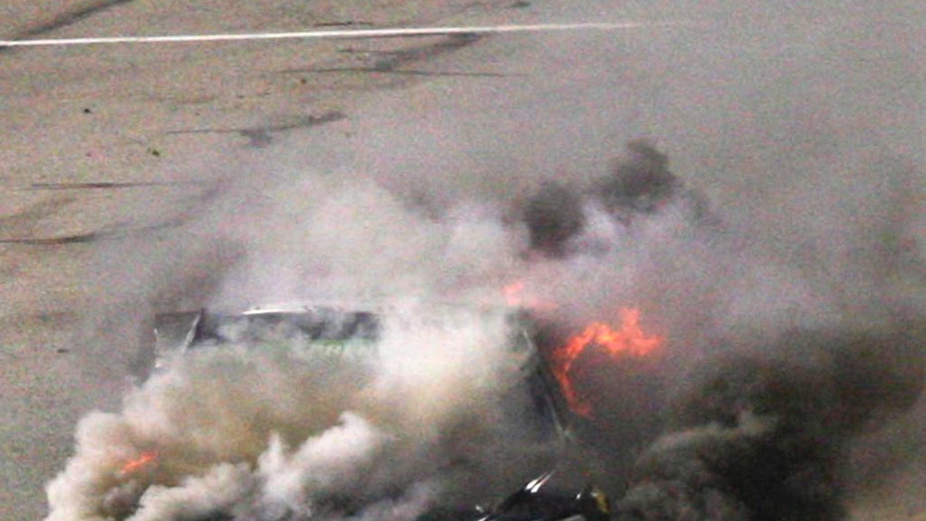 Reed Sorenson's car burns on pit row during the NASCAR Sprint Cup auto race at Richmond International Raceway in Richmond, Va., Saturday April 26, 2014. (AP Photo/Richmond Times-Dispatch, Dan Currier)