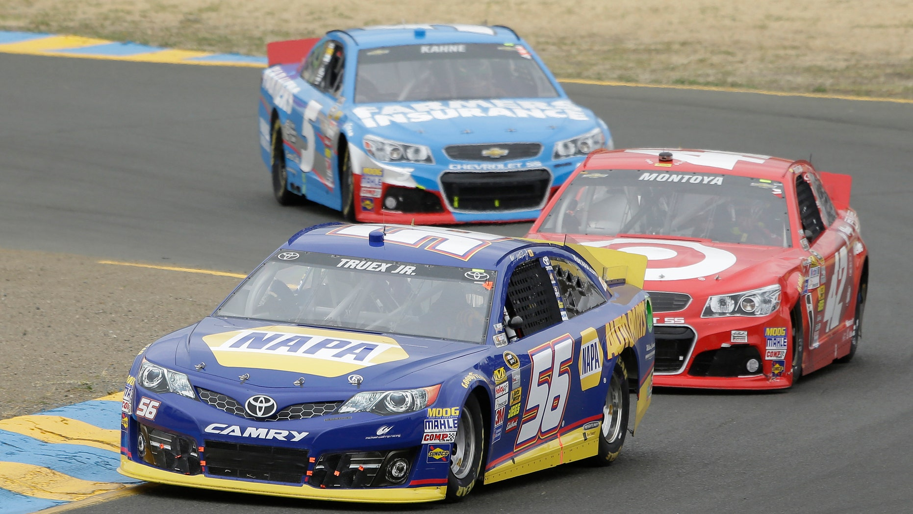 Martin Truex Jr. (56) leads Juan Pablo Montoyo, of Colombia, and Kasey Kahne through Turn 2 in a NASCAR Sprint Cup Series auto race on Sunday, June 23, 2013, in Sonoma, Calif. Truex Jr. won the race. (AP Photo/Eric Risberg)