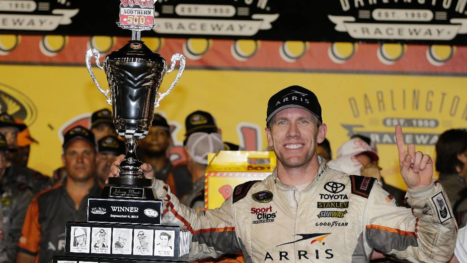 Carl Edwards celebrates in victory lane after winning a NASCAR Sprint Cup auto race at Darlington Raceway in Darlington, S.C., Monday, Sept. 7, 2015. (AP Photo/Terry Renna)