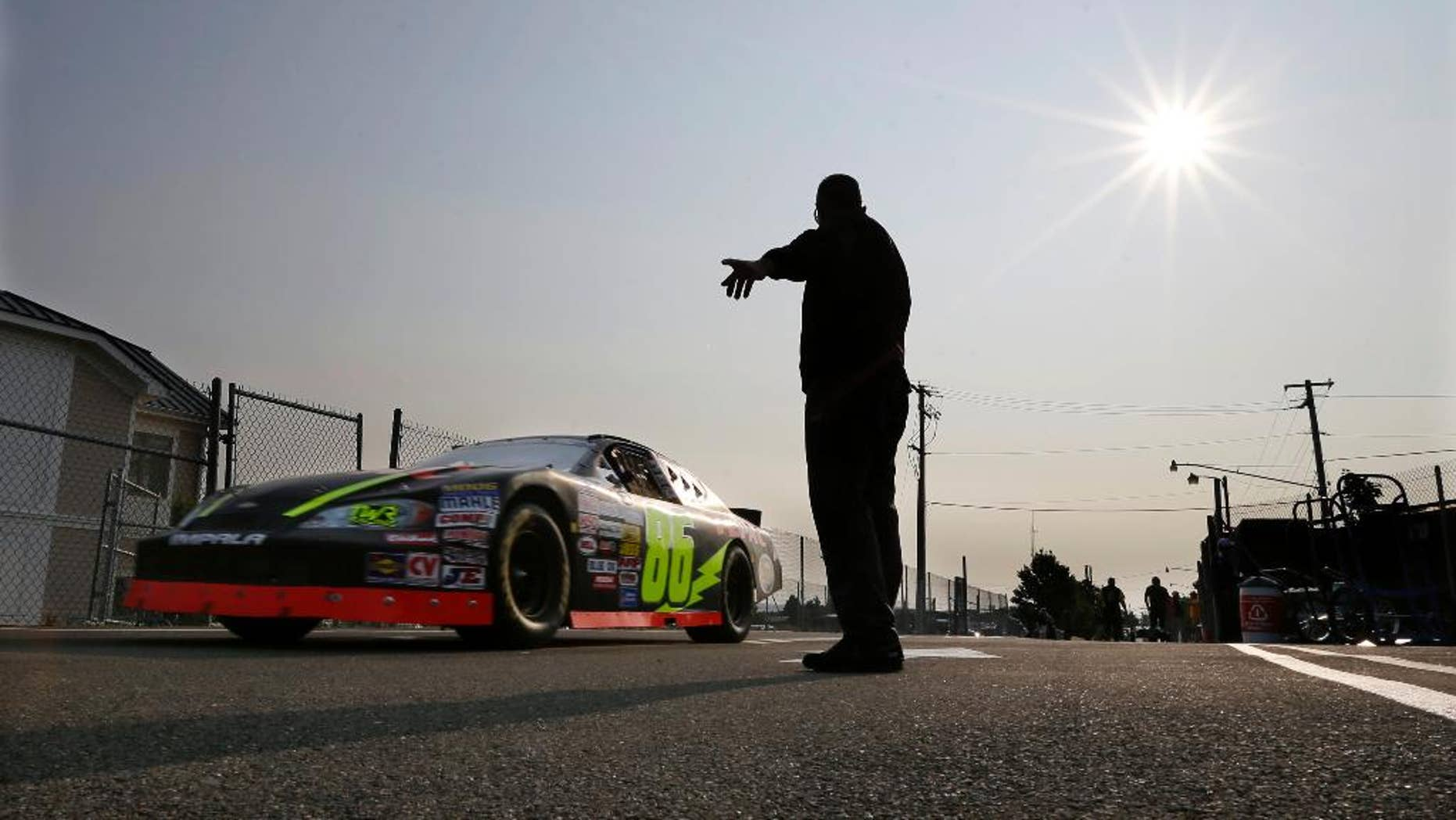 A race car heads out to the track during an early morning practice session for a NASCAR K&N Pro Series auto race at Watkins Glen International, Friday, Aug. 8, 2014, in Watkins Glen N.Y. (AP Photo/Mel Evans)