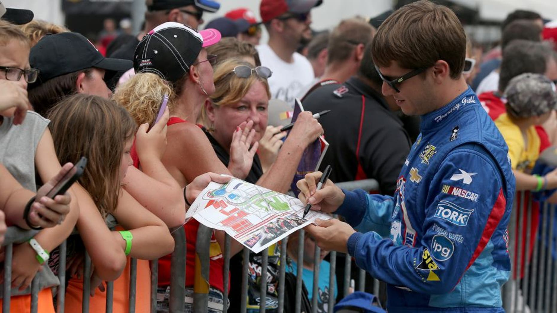 INDIANAPOLIS, IN - JULY 26: Landon Cassill, driver of the #40 Chevrolet, signs autographs for fans prior to the NASCAR Sprint Cup Series Crown Royal Presents the Jeff Kyle 400 at the Brickyard at Indianapolis Motor Speedway on July 26, 2015 in Indianapolis, Indiana. (Photo by Sean Gardner/NASCAR via Getty Images)