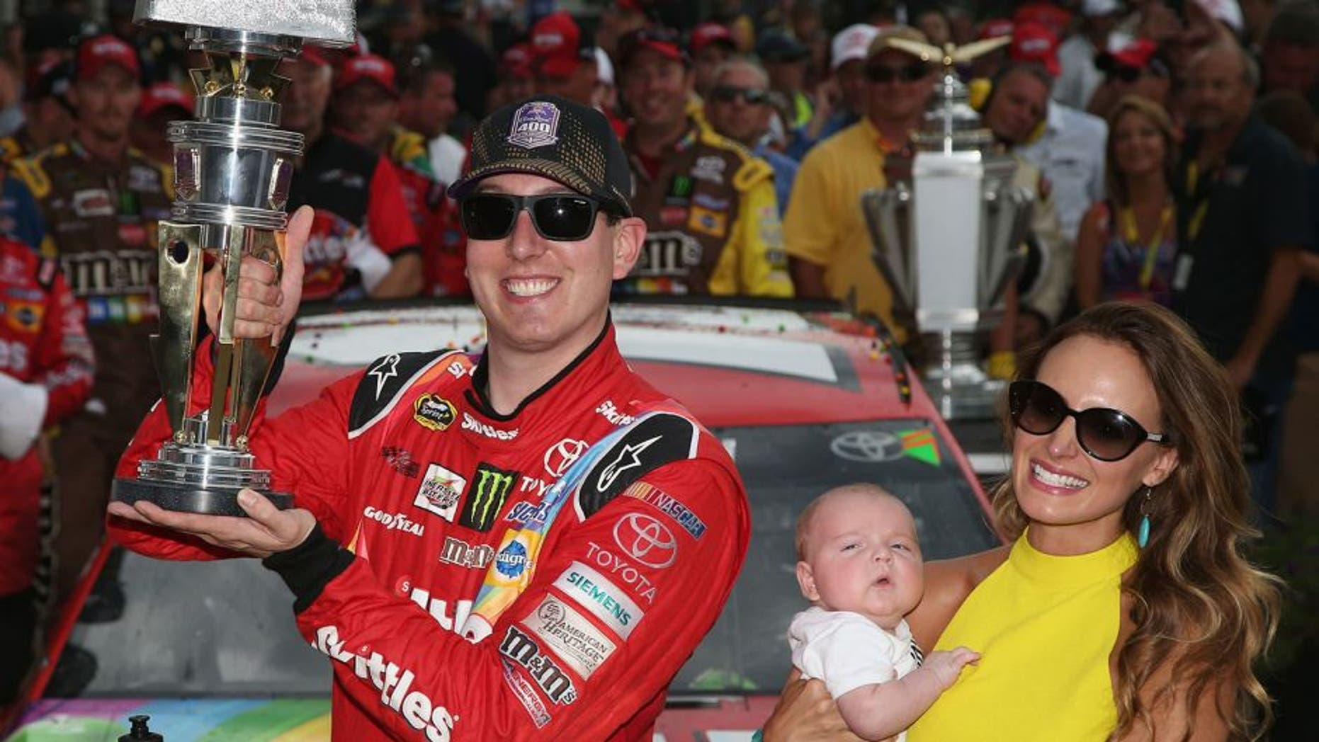 INDIANAPOLIS, IN - JULY 26: Kyle Busch, driver of the #18 Skittles Toyota, poses with the trophy in Victory Lane with wife Samantha and son Brexton Locke after winning the NASCAR Sprint Cup Series Crown Royal Presents the Jeff Kyle 400 at the Brickyard at Indianapolis Motor Speedway on July 26, 2015 in Indianapolis, Indiana. (Photo by Sean Gardner/NASCAR via Getty Images)