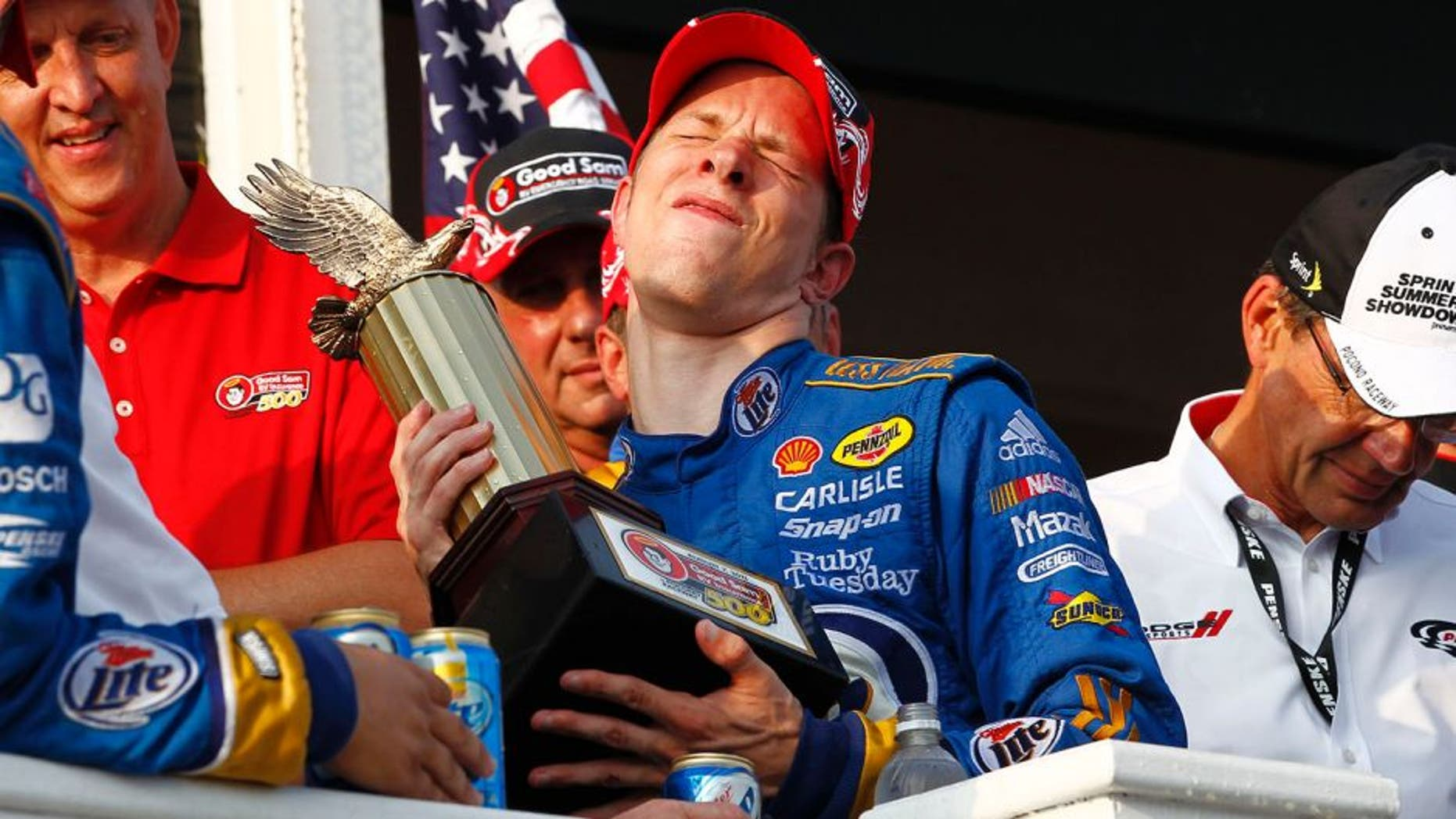 5-7 August, 2011, Long Pond, Pennsylvania USA Brad Keselowski winces in pain lifting the trophy (c)2011, Dan Streck LAT Photo USA