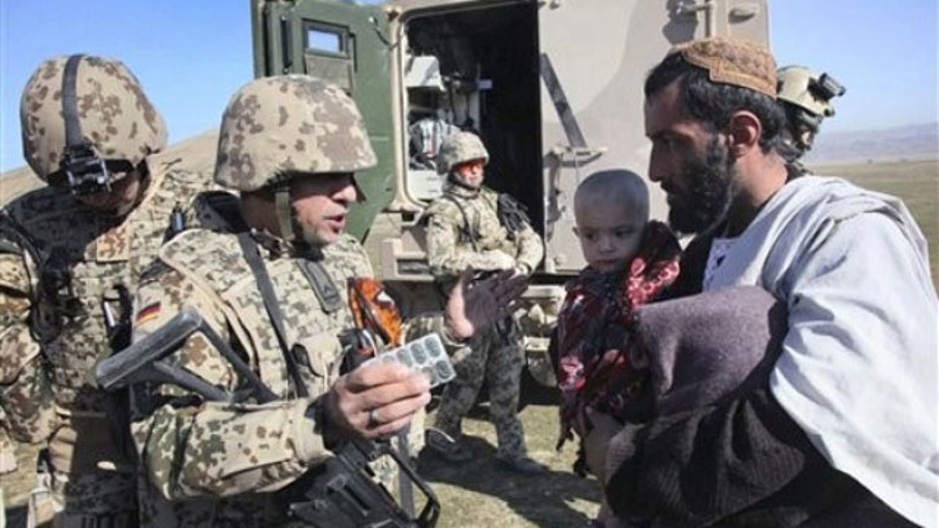 January 28, 2012: A German medic and soldier, center, part of a mobile medical team in the NATO- led International Security Assistance Force (ISAF) explains the usage of the medicine to father of an Afghan child patient during a joining ceremony of Taliban militants with the Afghan government in Baghlan, north of Kabul, Afghanistan.