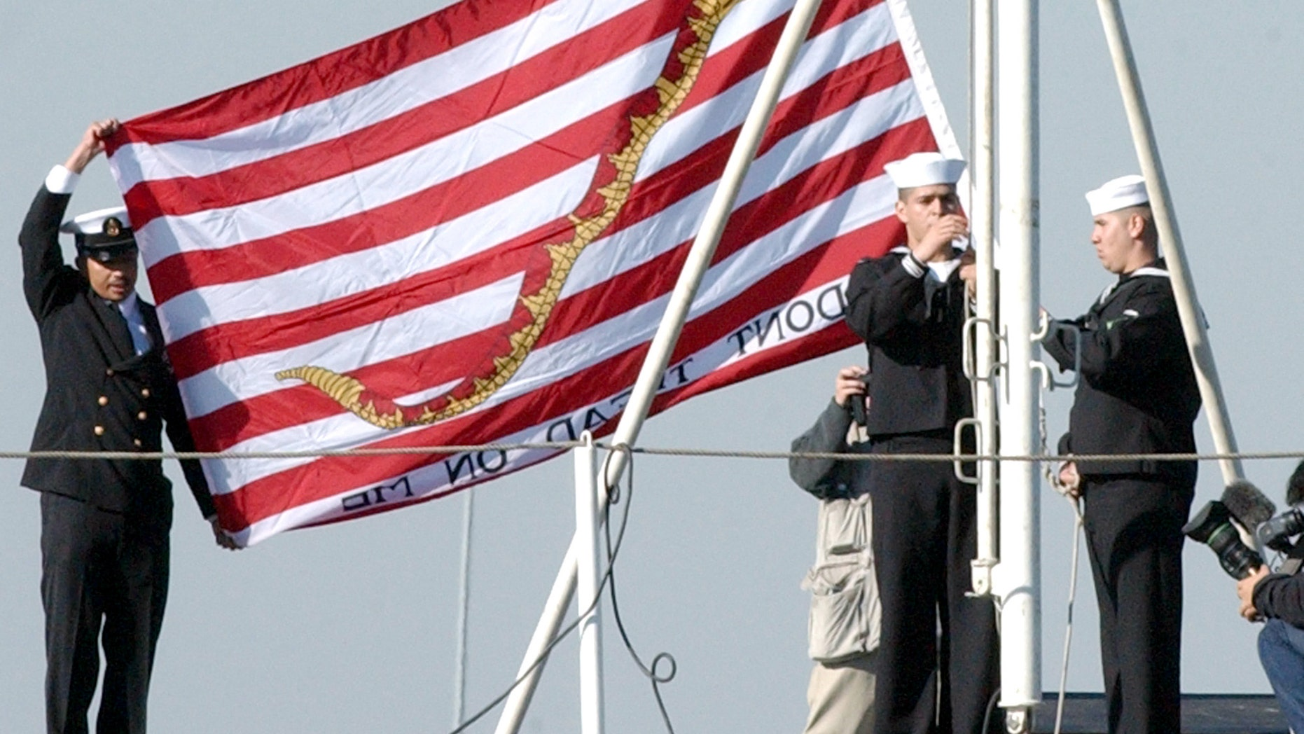 Official U.S. Navy file photo shows Sailors aboard the aircraft carrier USS Kitty Hawk (CV 63) raising the First Navy Jack.