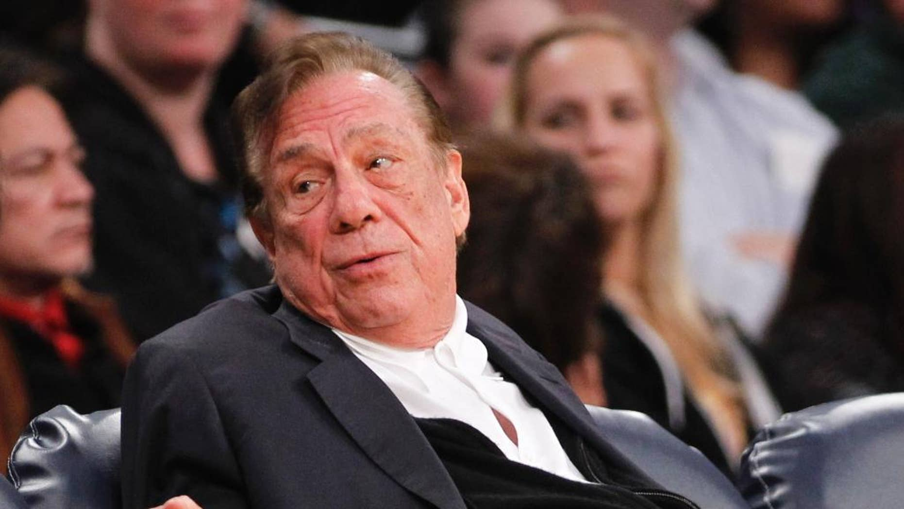 """FILE - In this Dec. 19, 2011, file photo, Los Angeles Clippers owner Donald Sterling gestures while watching the Clippers play the Los Angeles Lakers during an NBA preseason basketball game in Los Angeles. Taking the stand Tuesday, July 8, 2014, in a role he will resume on Wednesday, Sterling alternately declared his love for his wife, Shelly, with tears and then demeaned her as a woman intimidated by the """"bad NBA"""" and incapable of handling such a large financial transaction. (AP Photo/Danny Moloshok, File)"""