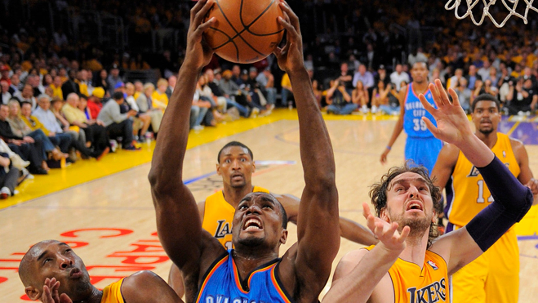 Oklahoma City Thunder forward Serge Ibaka of Congo, center, grabs a rebound as Los Angeles Lakers guard Kobe Bryant, left, and forward Pau Gasol of Spain look on during the first half in Game 3 of an NBA basketball playoffs Western Conference semifinal, Friday, May 18, 2012, in Los Angeles.  (AP Photo/Mark J. Terrill)