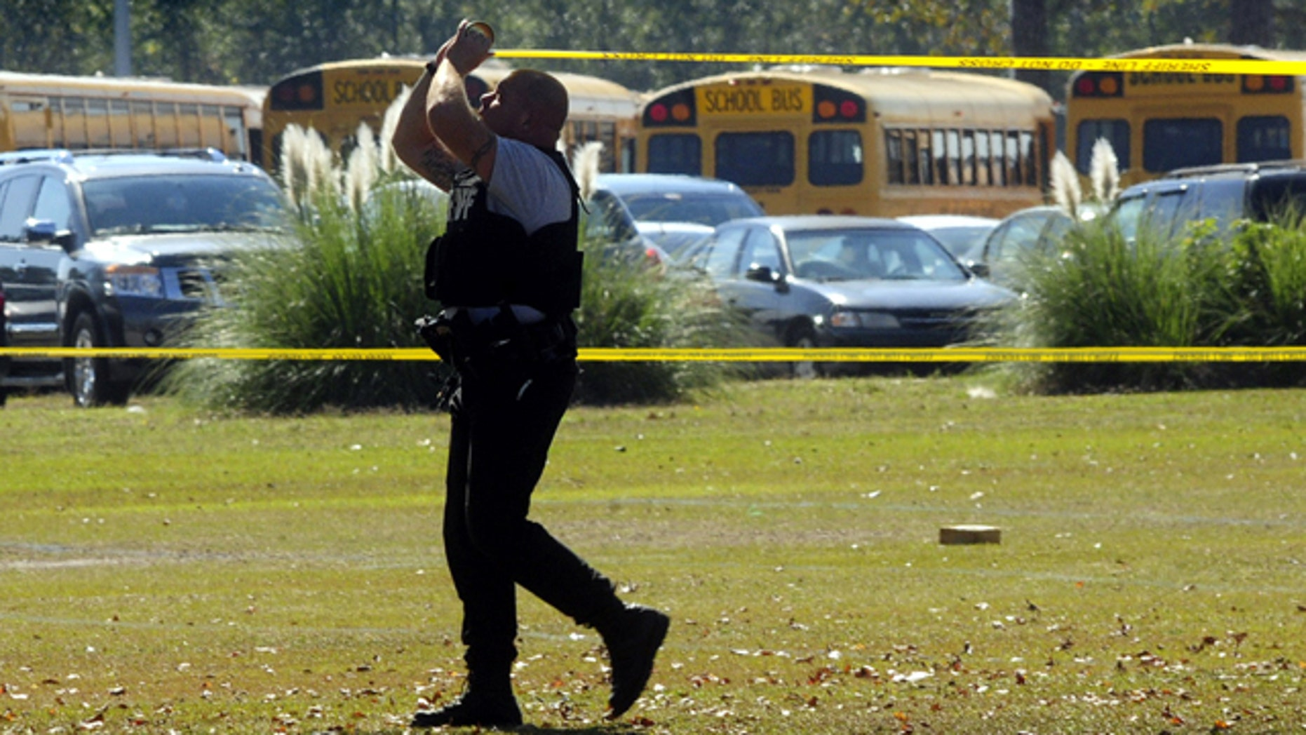 Oct. 24: A Cumberland County  Sheriffs deputy rolls crime scene tape around the scene after a  shooting at Cape Fear High School east of Fayetteville.