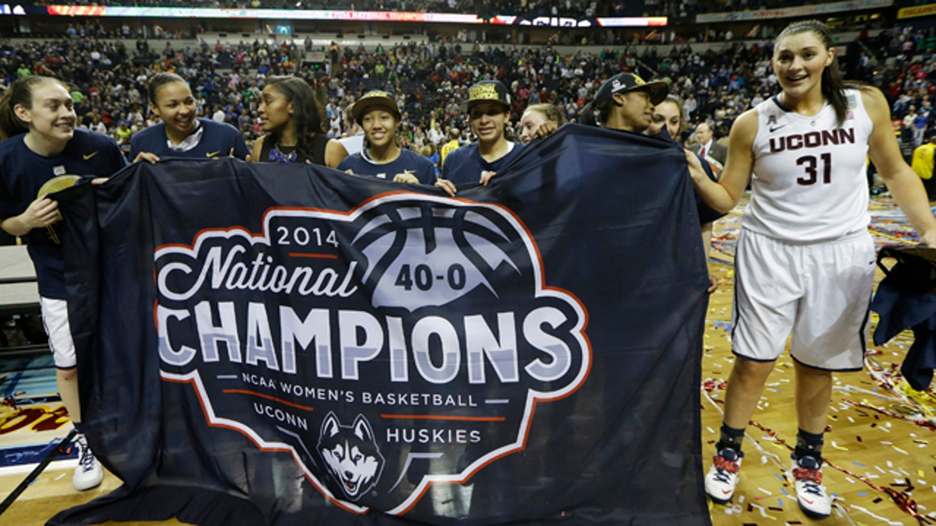 April 8, 2014: The Connecticut team celebrate their win over Notre Dame in  the championship game in the Final Four of the NCAA women's college basketball tournament in Nashville, Tenn. (AP Photo/Mark Humphrey)